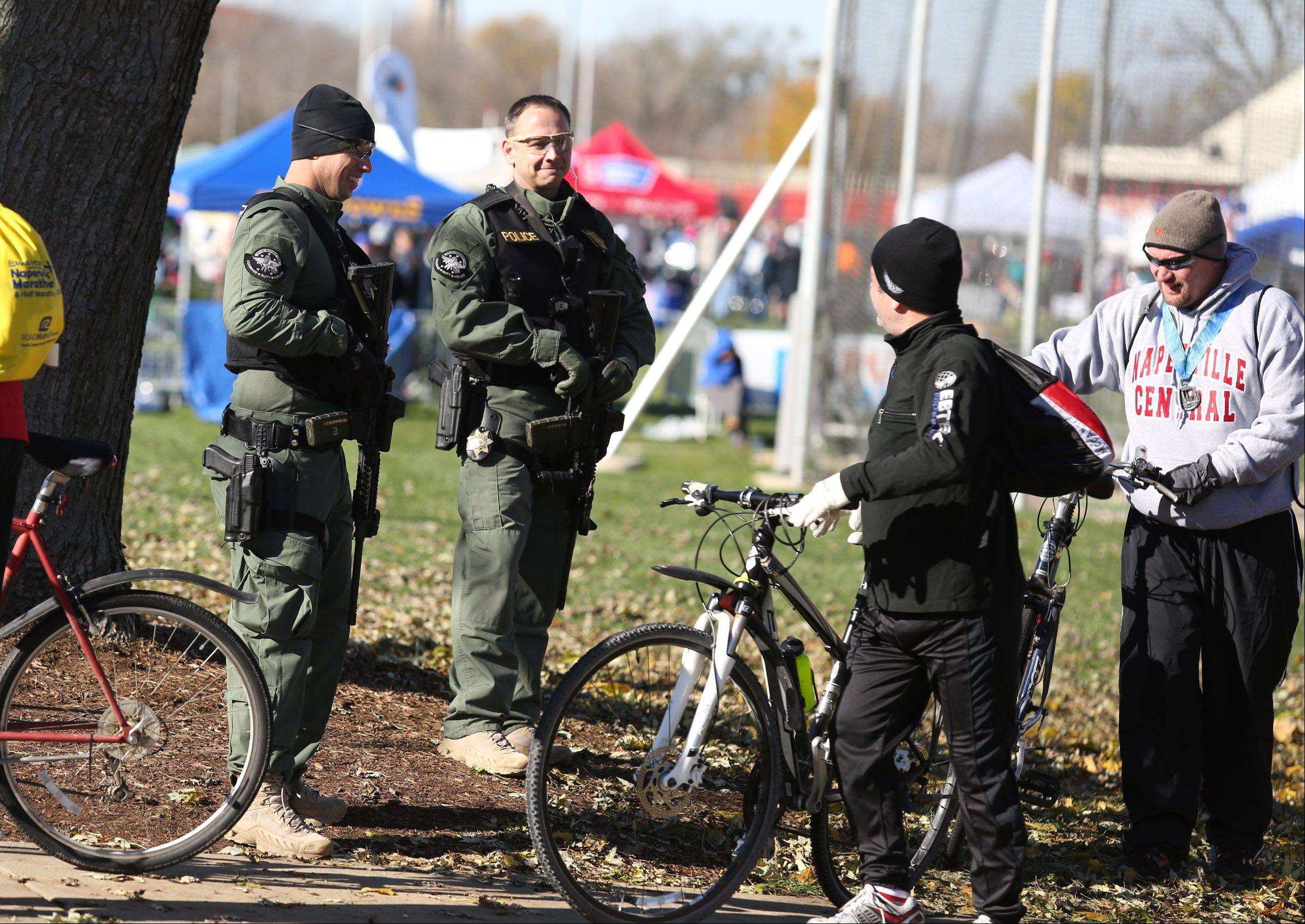 Cyclist talk to police officers near the finish of the Edward Hospital Naperville Marathon on Sunday, November 10, 2013.