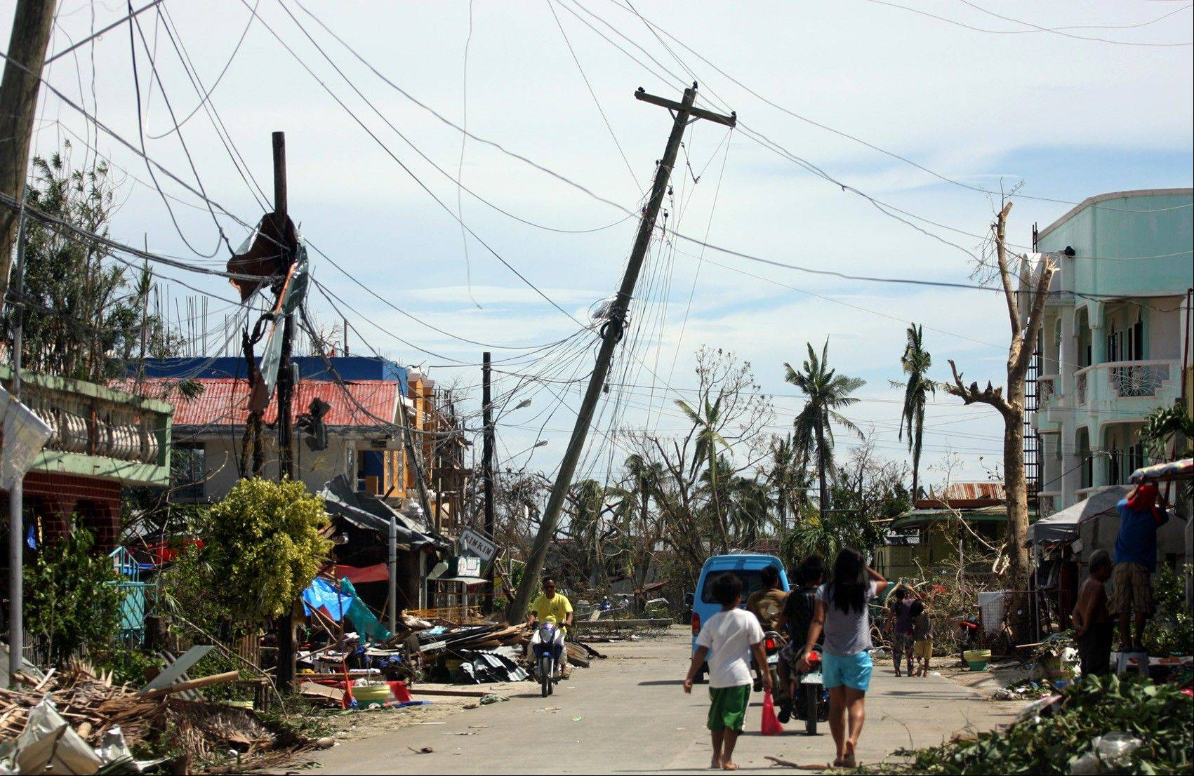 Residents walk past the devastation caused by Typhoon Haiyan in Daanbantayan town, north Cebu, central Philippines. Typhoon Haiyan, one of the most powerful storms on record, slammed into six central Philippine islands on Friday, leaving a wide swath of destruction and scores of people dead.