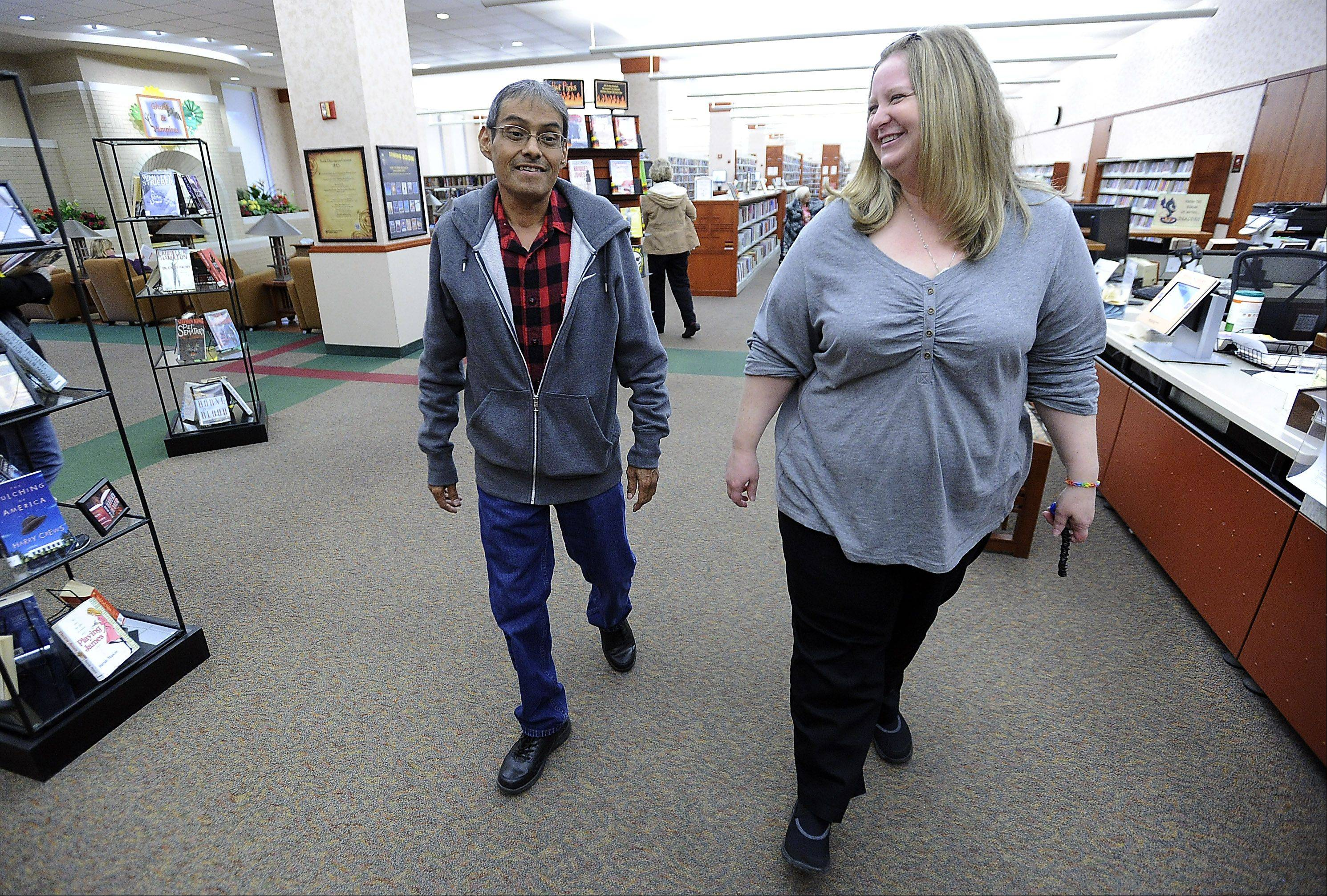 Cindy Barger, serials supervisor at the Schaumburg Township District Library, talks to her friend and co-worker Freddie Martinez about his recent liver transplant and his becoming the 1,500th liver recipient at Northwestern Memorial Hospital. Barger helped Martinez through his difficult times both at home and in the hospital.