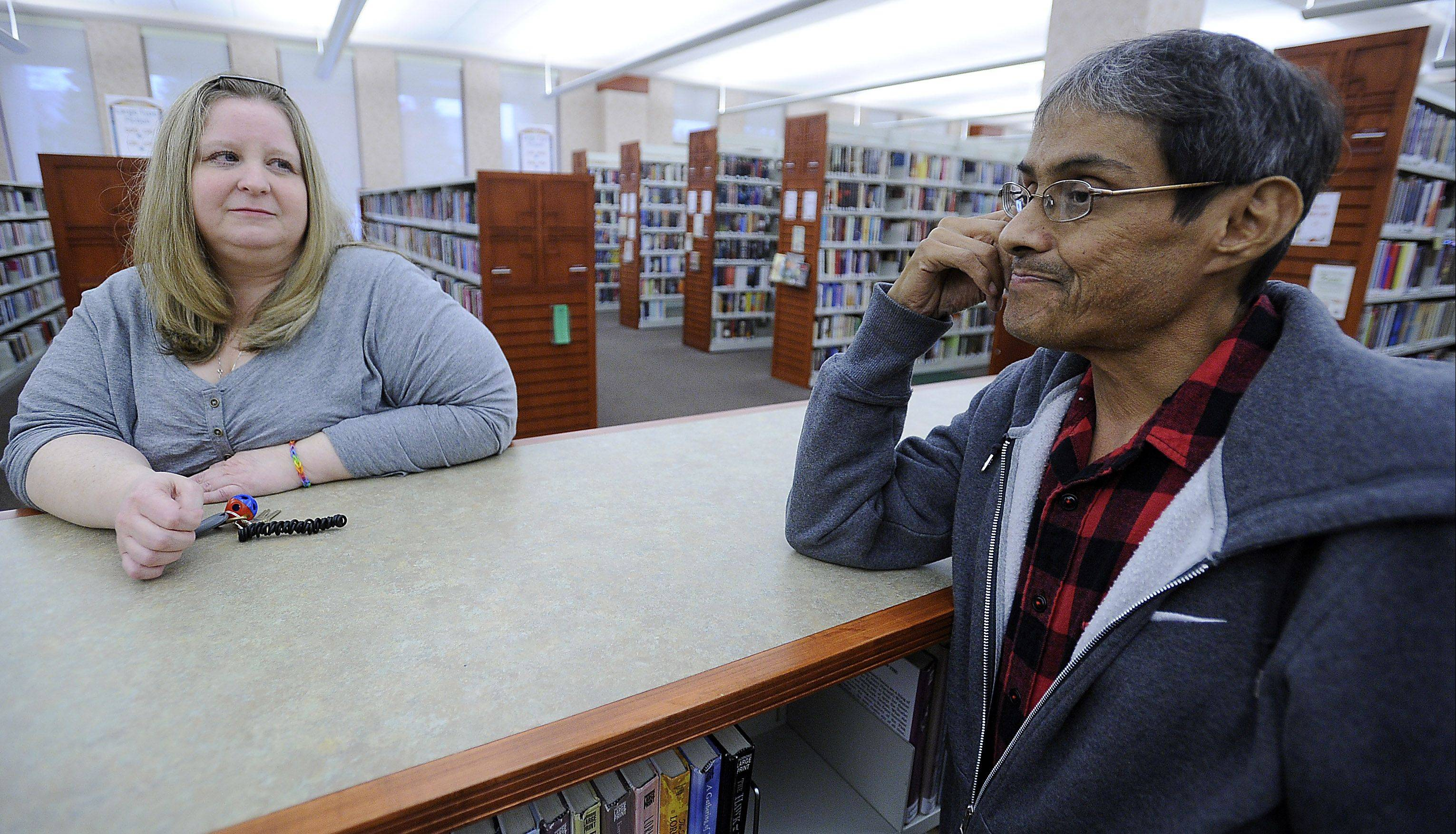 Cindy Barger, serials supervisor at the Schaumburg Township District Library, looks on as her friend and co-worker Freddie Martinez gets choked up while discussing his recent liver transplant. Barger helped Martinez through his difficult times both at home and in the hospital.