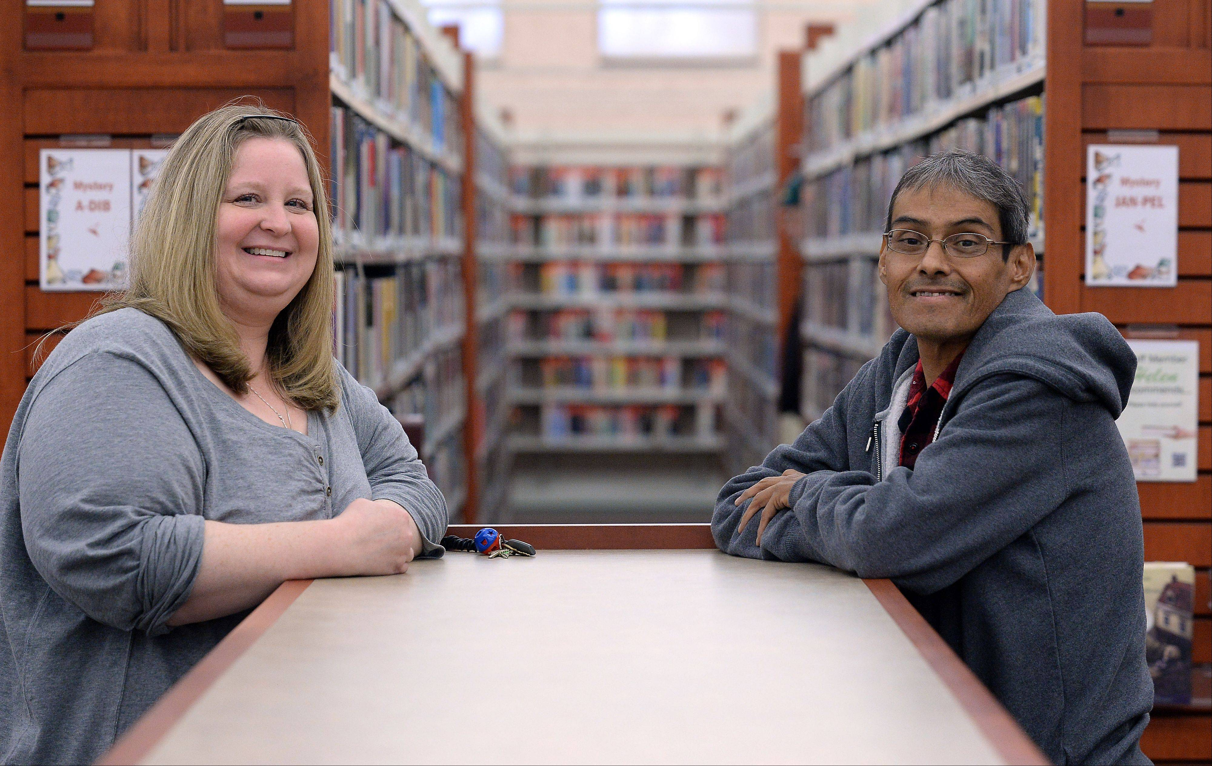 Cindy Barger, serials supervisor at the Schaumburg Township District Library, shares a smile with friend and co-worker Freddie Martinez as they talk about his recent liver transplant. Barger helped Martinez through his difficult times both at home and in the hospital.