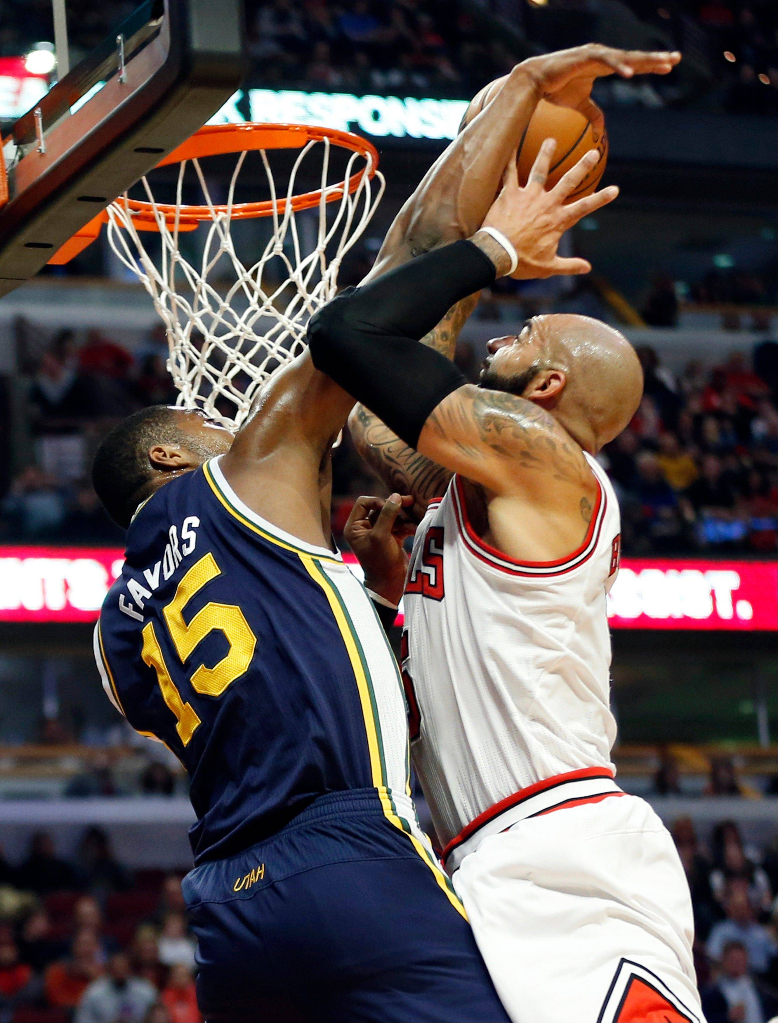 Carlos Boozer, right, goes to the basket against Utah Jazz forward Derrick Favors (15) during the first quarter of an NBA basketball game in Chicago, Friday, Nov. 8, 2013.