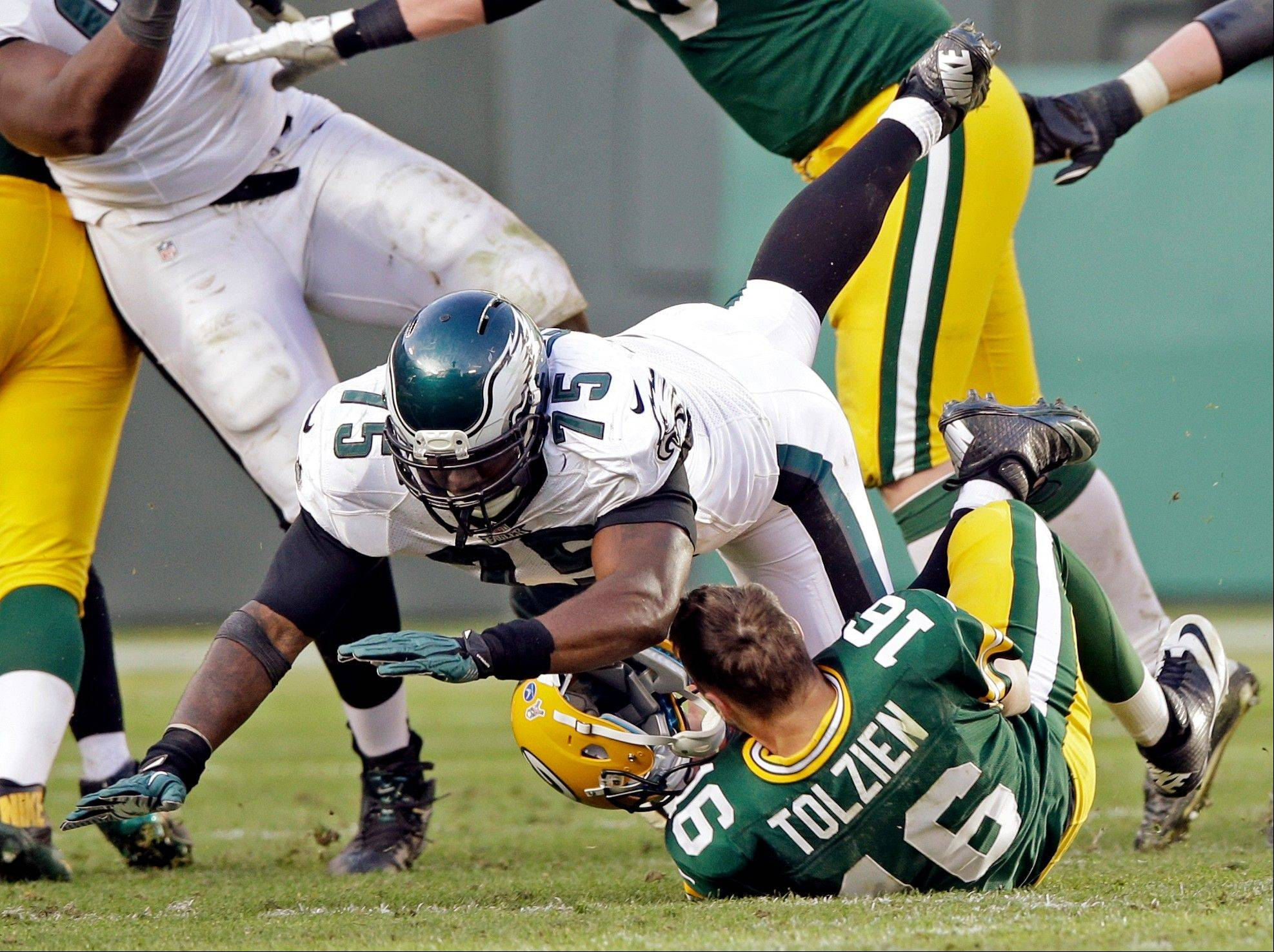 Green Bay Packers quarterback Scott Tolzien loses his helmet as he is sacked by Philadelphia Eagles' Vinny Curry during the second half of an NFL football game Sunday, Nov. 10, 2013, in Green Bay, Wis.