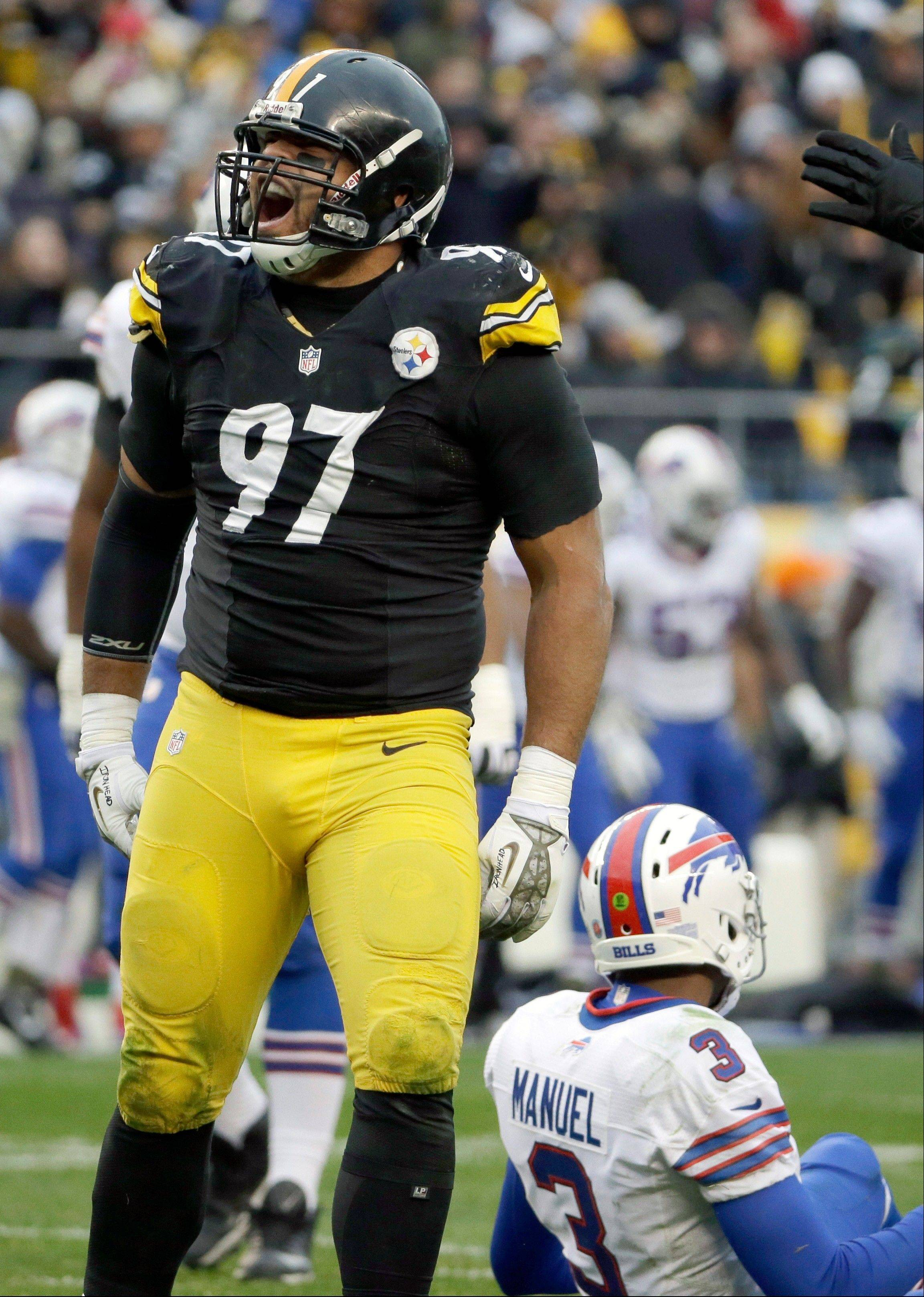 Pittsburgh Steelers' Cameron Heyward, left, reacts after tackling Buffalo Bills' EJ Manuel during the second half of an NFL football game on Sunday, Nov. 10, 2013, in Pittsburgh.