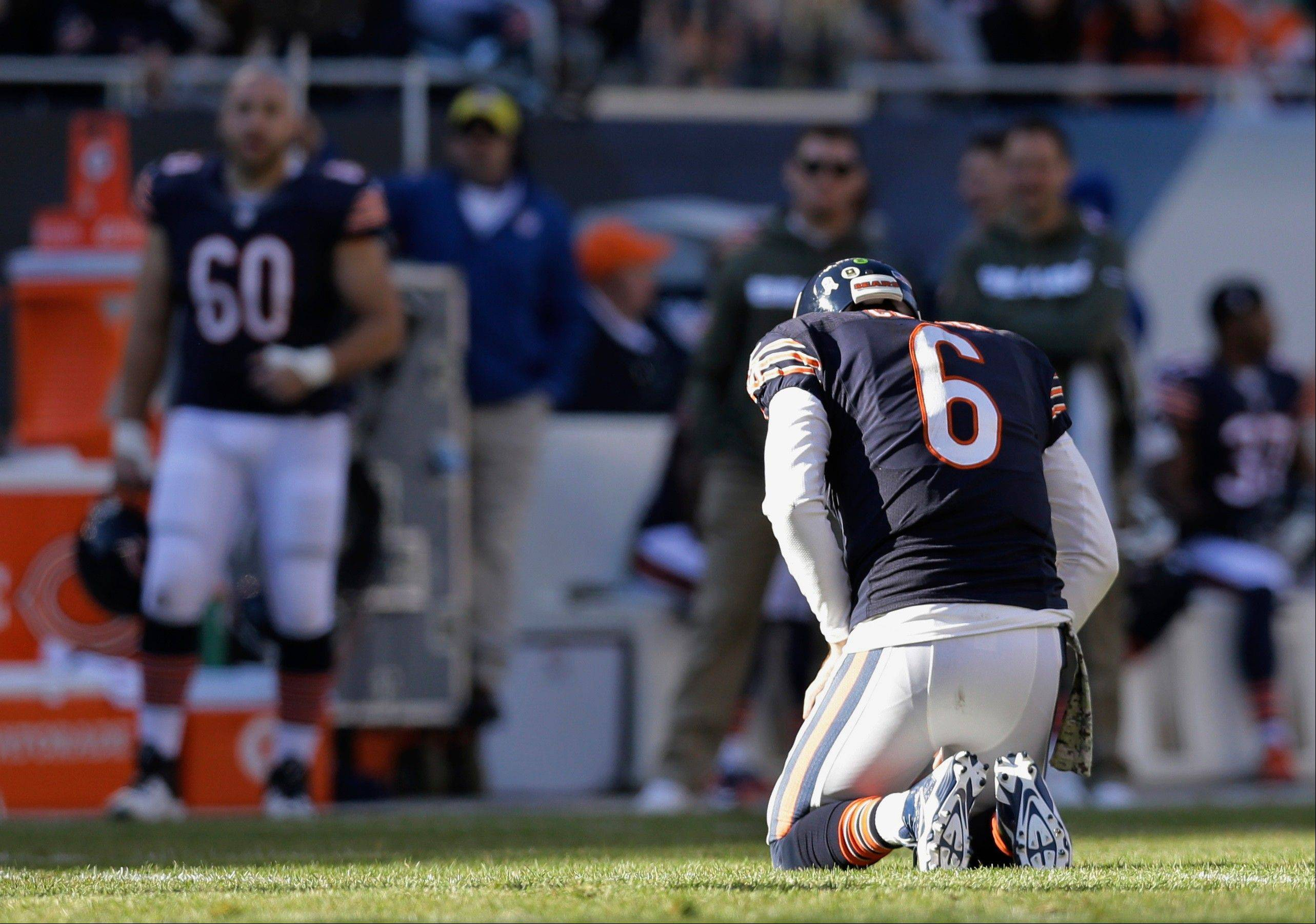 Bears quarterback Jay Cutler kneels on the field after a play during the second half of an NFL football game against the Detroit Lions, Sunday, Nov. 10, 2013, at Soldier Field.