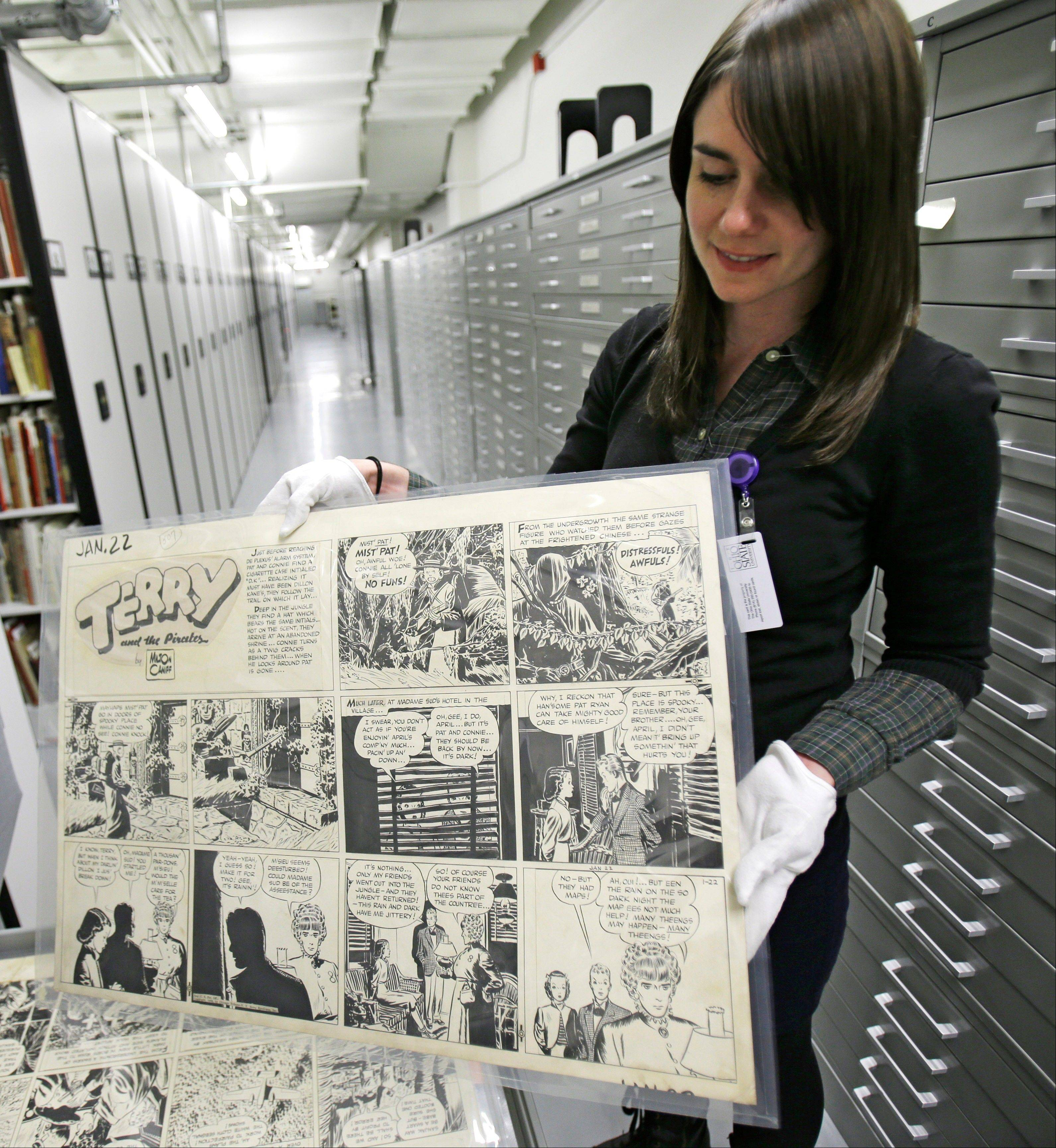 Caitlin McGurk holds up a cartoon titled �Terry and the Pirates� by Milton Caniff at the Billy Ireland Cartoon Library & Museum in Columbus, Ohio.