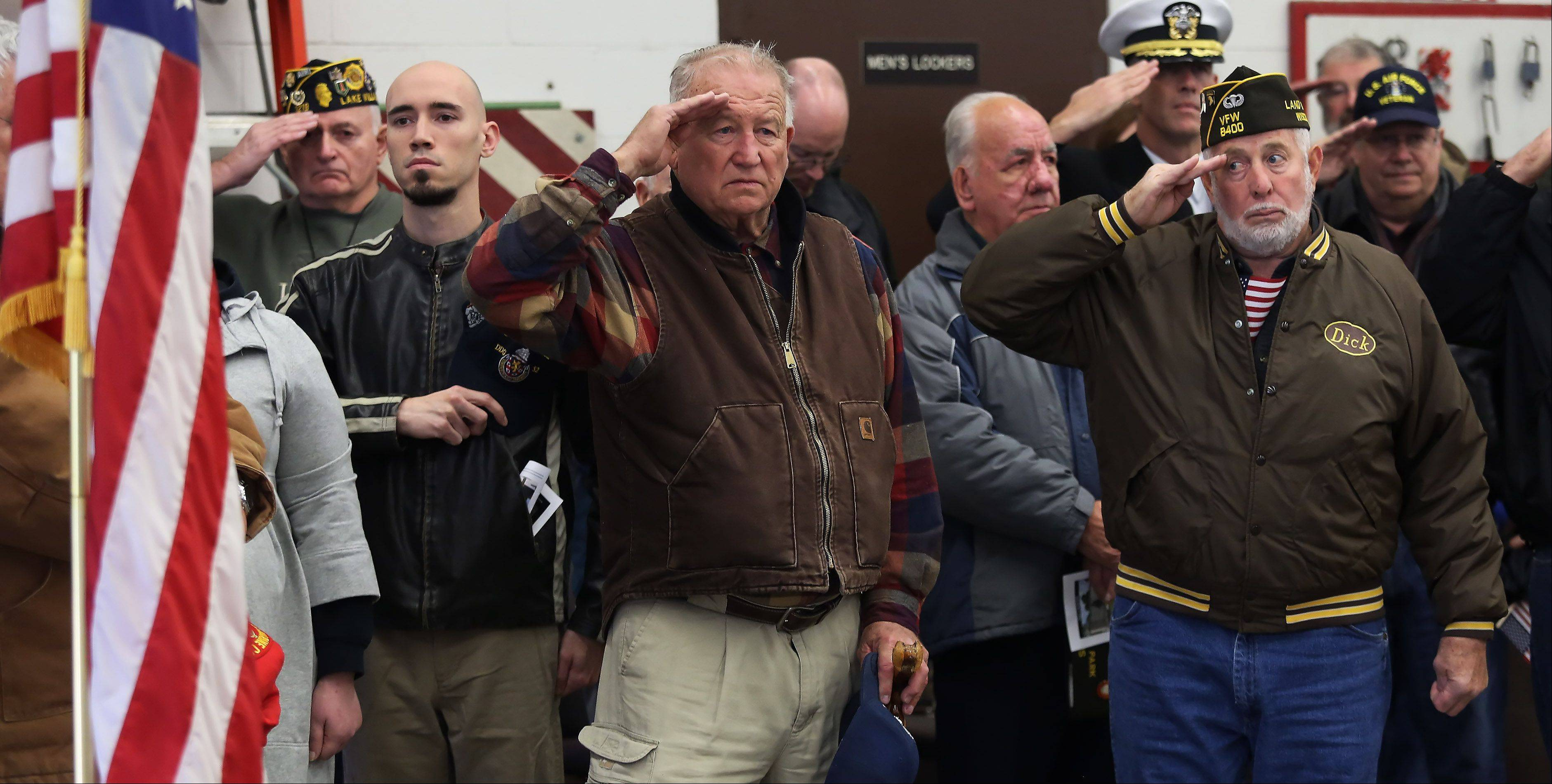 Veterans stand at attention during the playing of Taps at Monday� Veterans Day ceremony at the Lindenhurst Municipal Center and Veterans Memorial. The ceremony honored veterans and their families and featured several speakers, including Capt. R. Scott Laedlein, commanding officer of Navy Operational Support Command for Chicago.