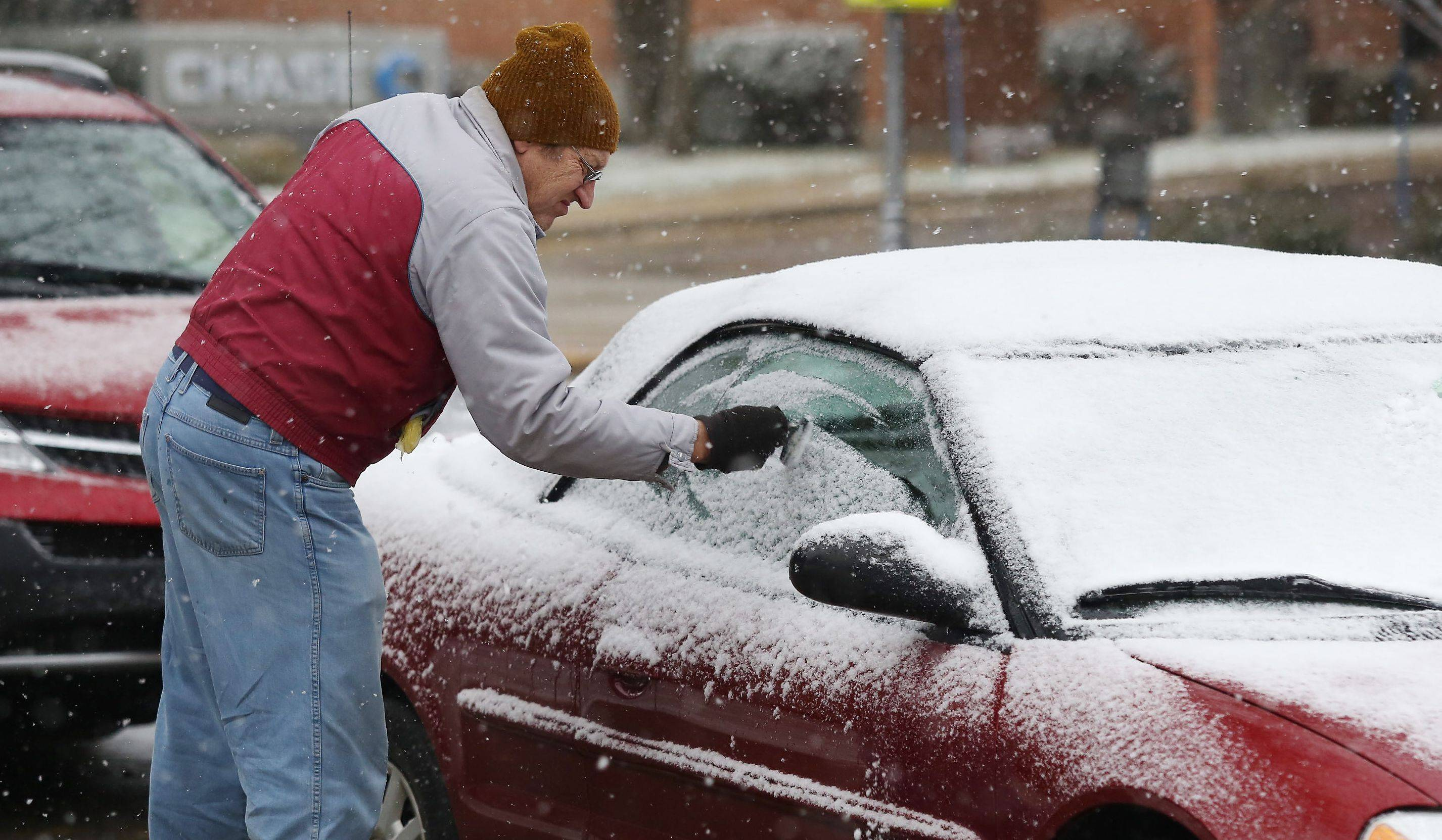 Paul Frisch of Lake Forest clears the snow from his car windows near Cook Park in Libertyville.
