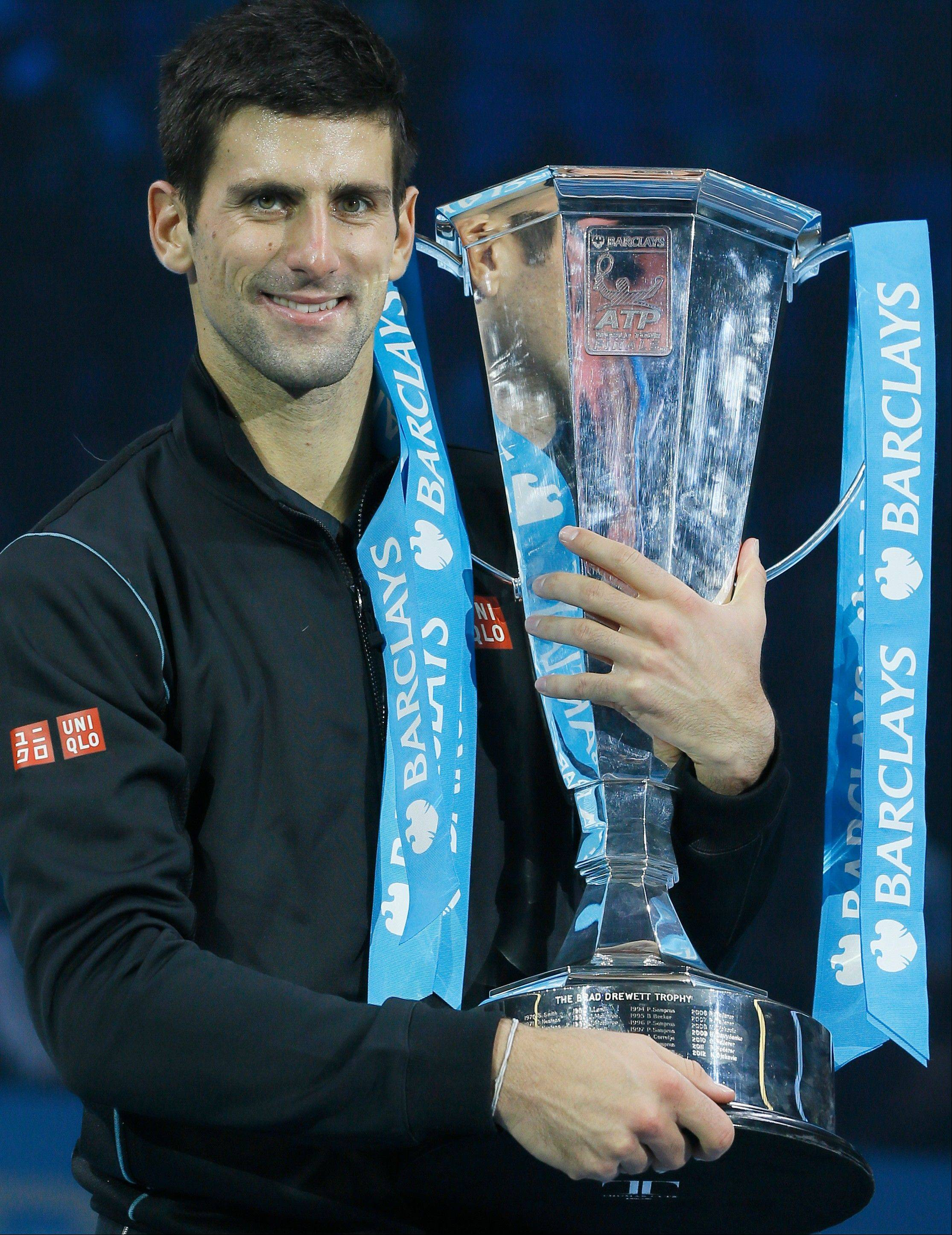 Novak Djokovic of Serbia holds up the ATP World Tour Finals tennis trophy as he poses for photographers after defeating Rafael Nadal of Spain at the O2 Arena in London, Monday, Nov. 11, 2013.