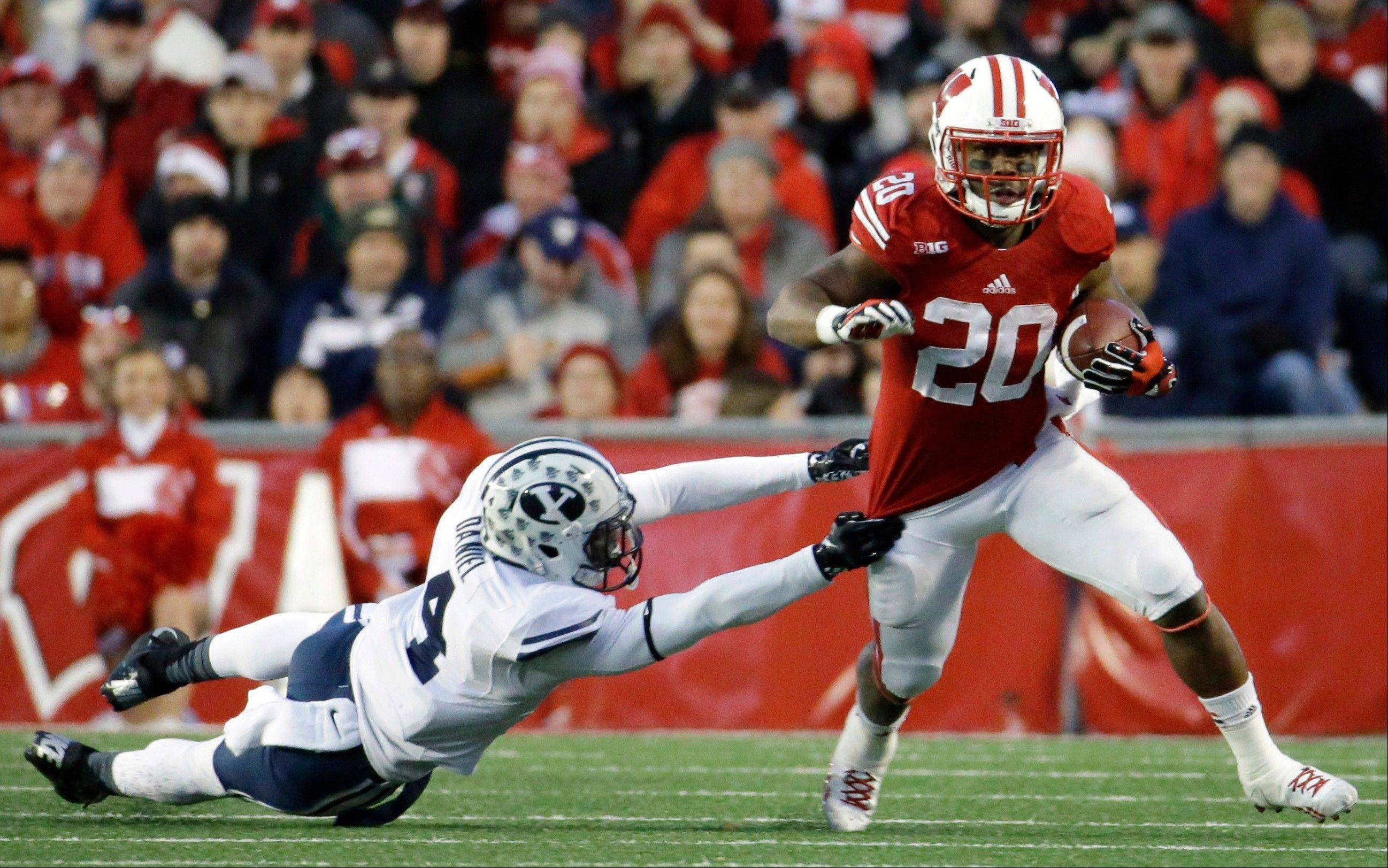 Wisconsin�s James White, right, gets past Brigham Young�s Robertson Daniel during the second half of Saturday�s game in Madison. Wisconsin won 27-17.