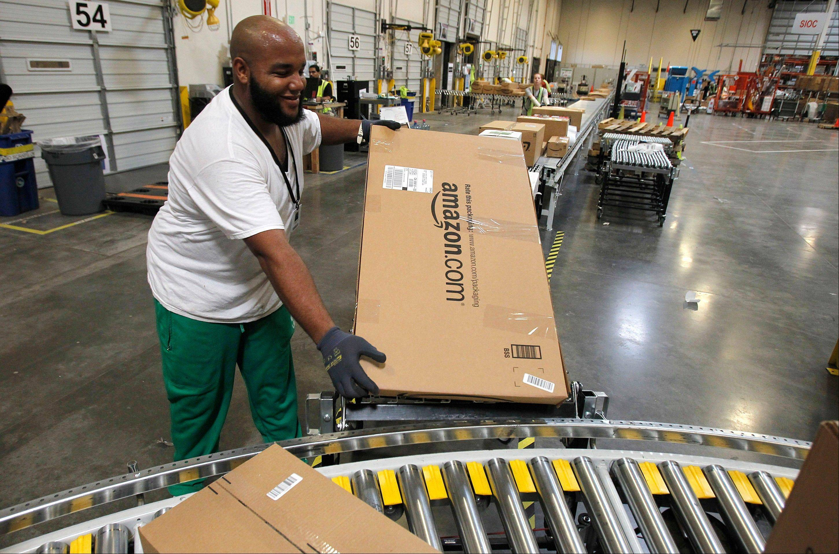 A worker places a package in the correct shipping area at an Amazon.com fulfillment center, in Goodyear, Ariz. Amazon is teaming with the U.S. Postal Service to deliver packages on Sundays.