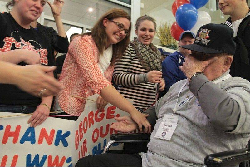 George Houchin of Waukegan is overcome with emotion as he's greeted at Midway International Airport upon his return from seeing the World War II Memorial in Washington, D.C. A Culver's manager in Zion encouraged Houchin to go on the Honor Flight and then accompanied him.
