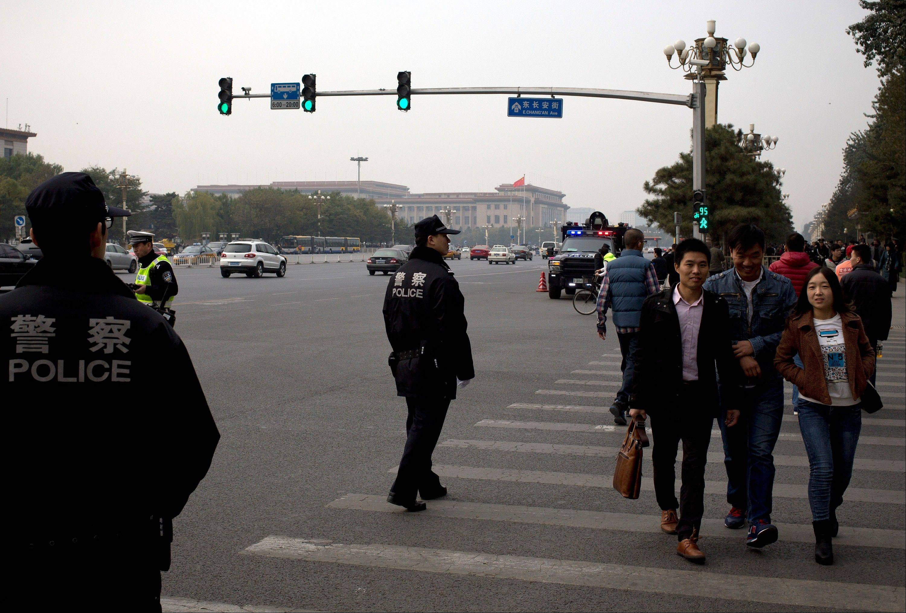 Chinese policemen stand guard as visitors head to Tiananmen Square during a gathering of the 205-member Central Committee's third annual plenum in Beijing Saturday. Reform advocates are looking to China's leaders to launch a new era of change by giving entrepreneurs a bigger role in the state-dominated economy and farmers more control over land at a policymaking conference that opened Saturday.