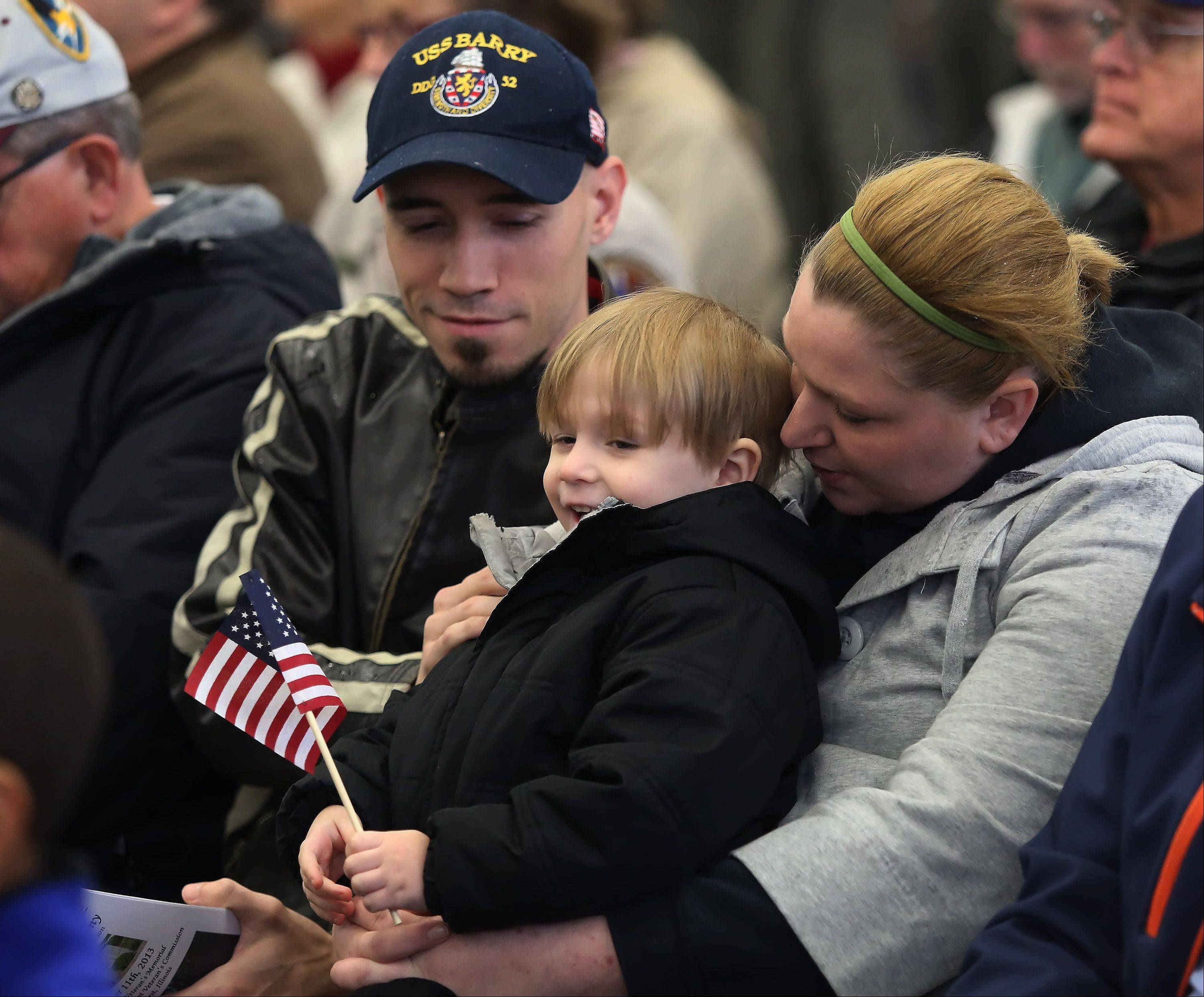 Alex Norlin, 4, of Lake Zurich waves a flag as he sits with his parents Samantha and retired Navy Specialist Jonathan Norlin during the Veterans Day ceremony Monday at Lindenhurst Municipal Center and Veteran's Memorial.