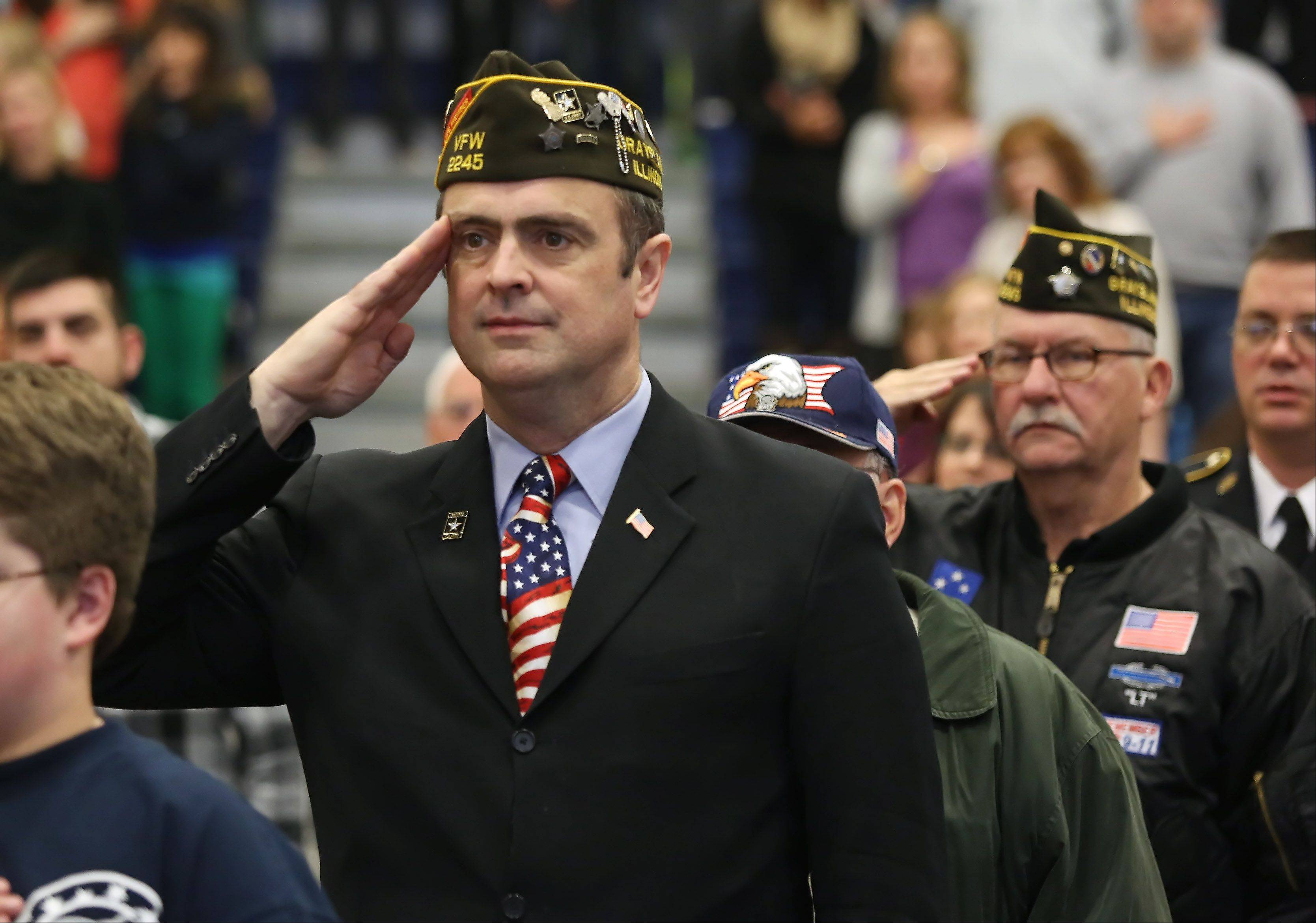 Former Army Col. Paul Ahern of VFW Post 2245, left, joins other veterans as he salutes during the playing of the National Anthem at the Veterans Day assembly Monday at Frederick School in Grayslake.