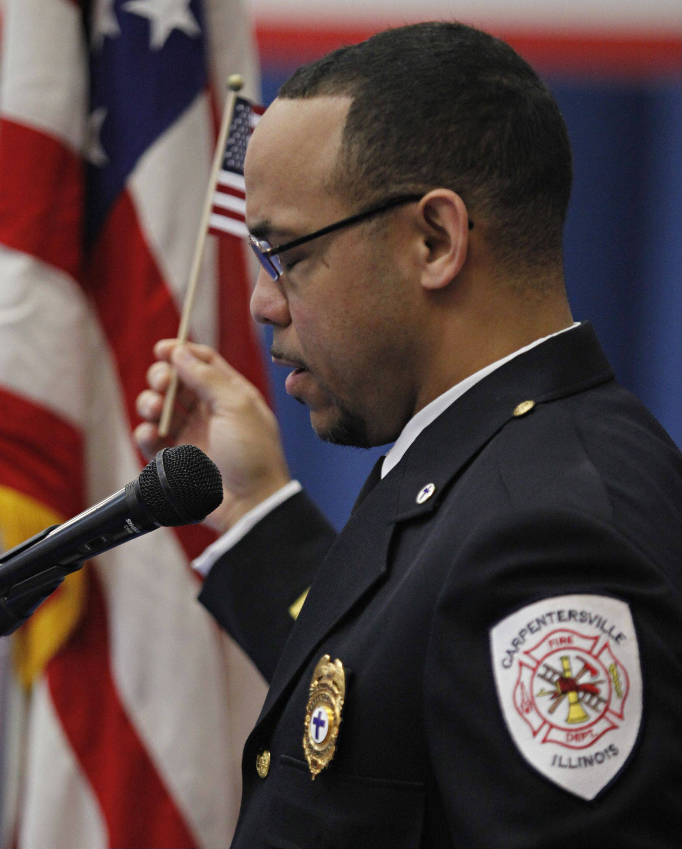 Carpentersville Fire Department chaplain Dexter Ball leans a prayer during the Veterans Day ceremony at Parkview Elementary Monday in Carpentersville.