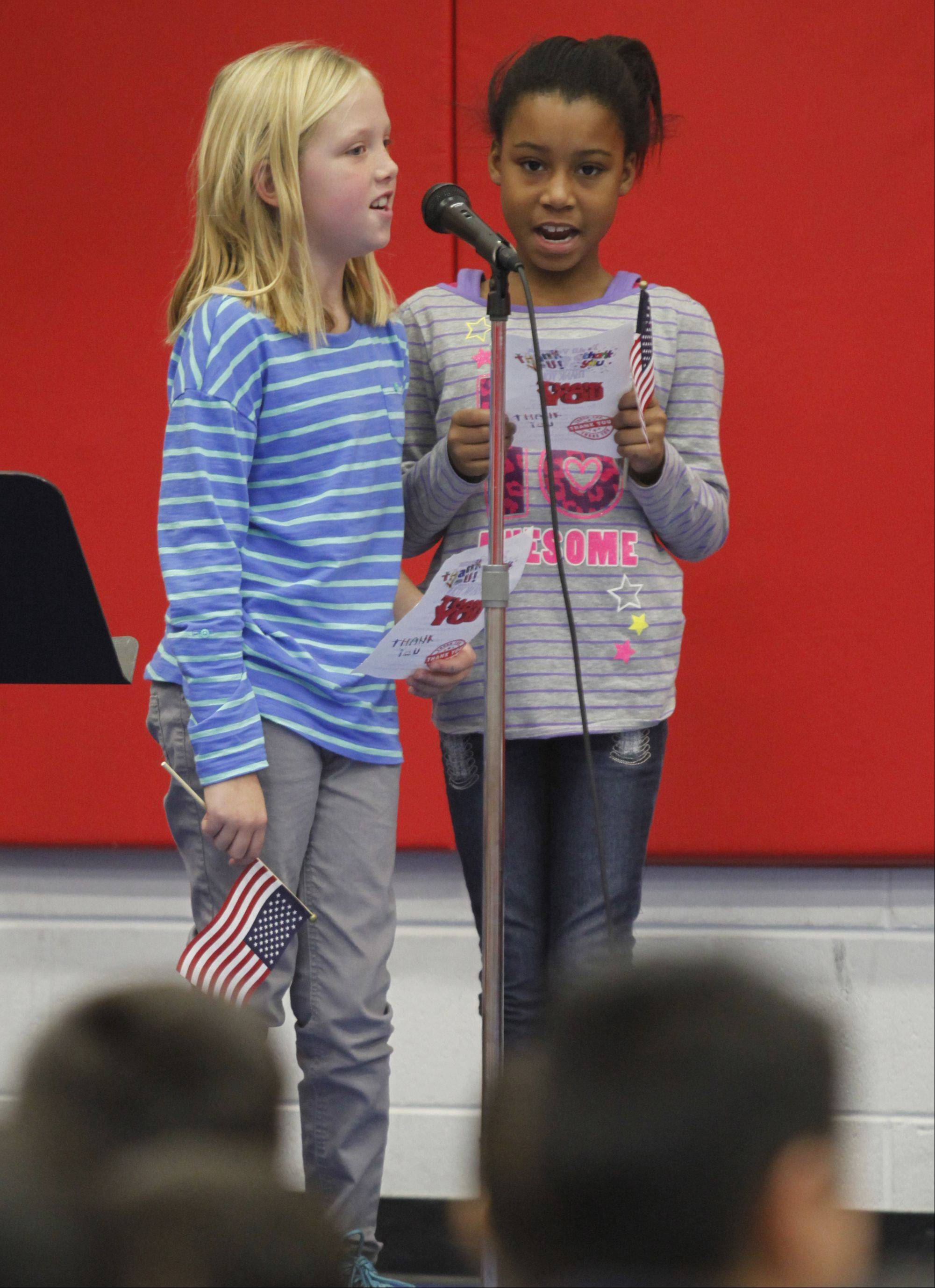 "Third-graders Rheanna Niemiec, left, and Myracle Stewart sing ""Thank You, Veterans"" during the Veterans Day ceremony Monday at Parkview Elementary in Carpentersville."