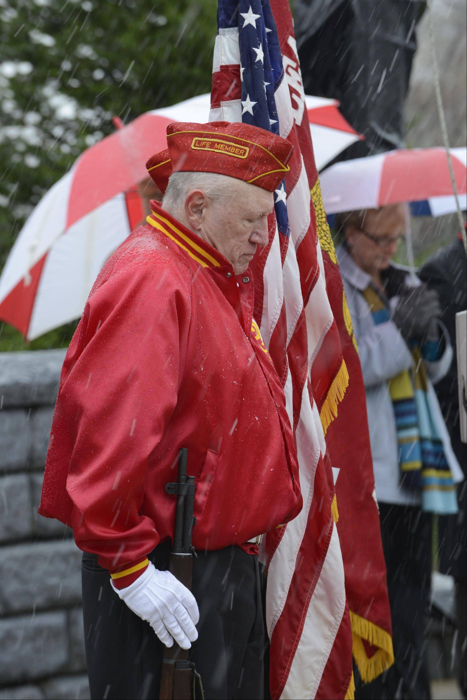 North Aurora Honor Guard member Robert L. Thornton bows his head in prayer during a Veterans Day ceremony Monday at the Veterans Memorial on Willow Way in North Aurora. He served in the Marine Corp.