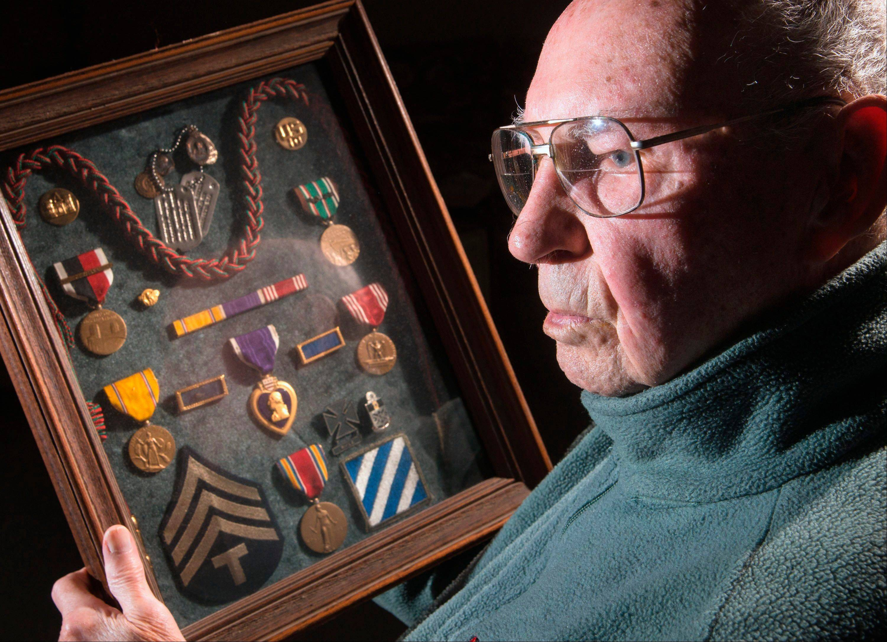 "World War II veteran Charles F. ""Chick"" Bruns, of Champaign, Ill., looks at the medals and patches from his years in the Army. Bruns wrote a ""blog"" during World War II that is only now being published with the help of a website created by his son."