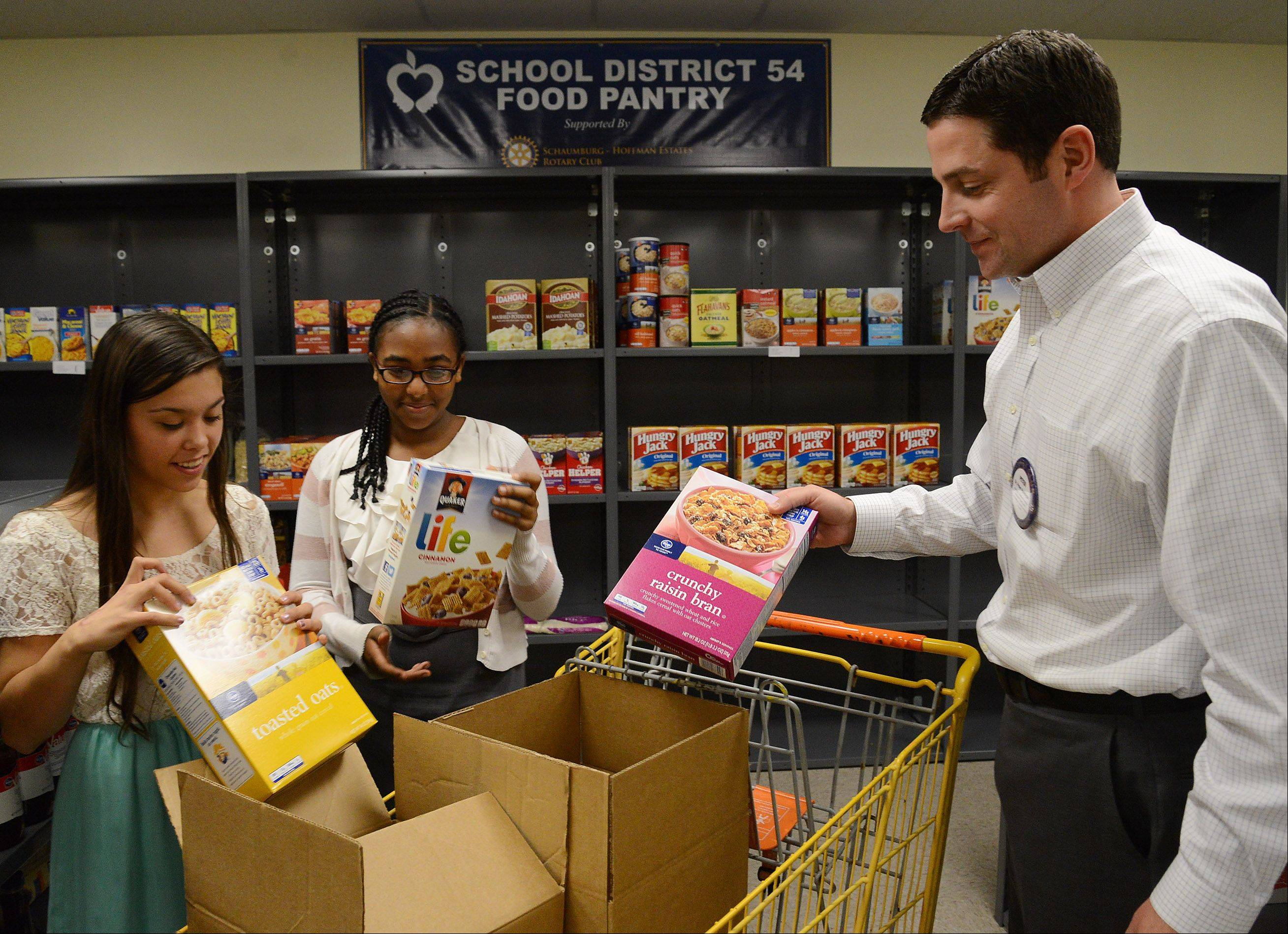 Keller eighth-graders Morgan Krug, left, and Keneni Godana help Rotary member and District 54 Assistant Superintendent Pete Hannigan stock shelves, as they get ready to open the food pantry.