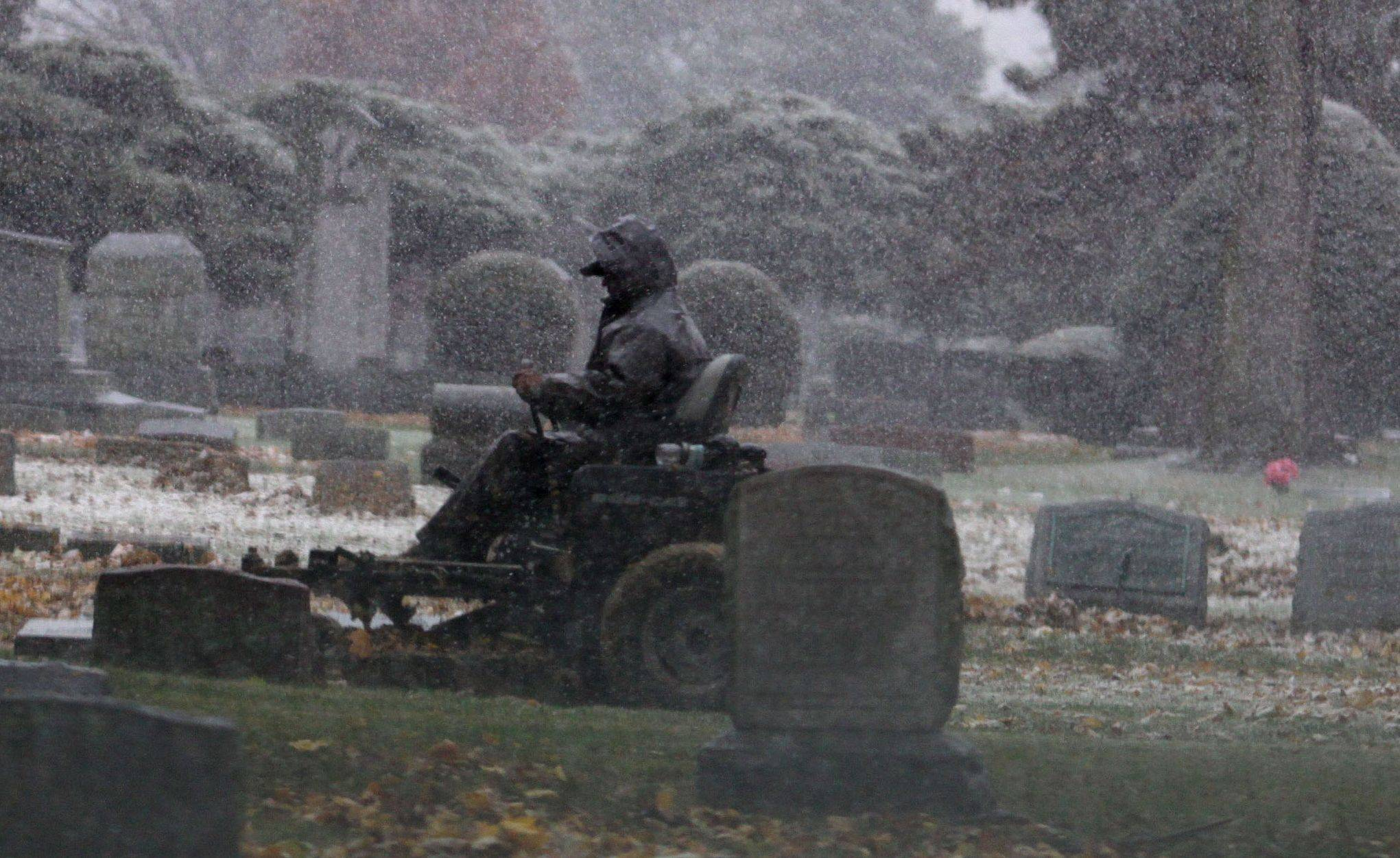 Rain turns into light snow Monday afternoon as maintenance crews work on the grounds of Wheaton Cemetery.