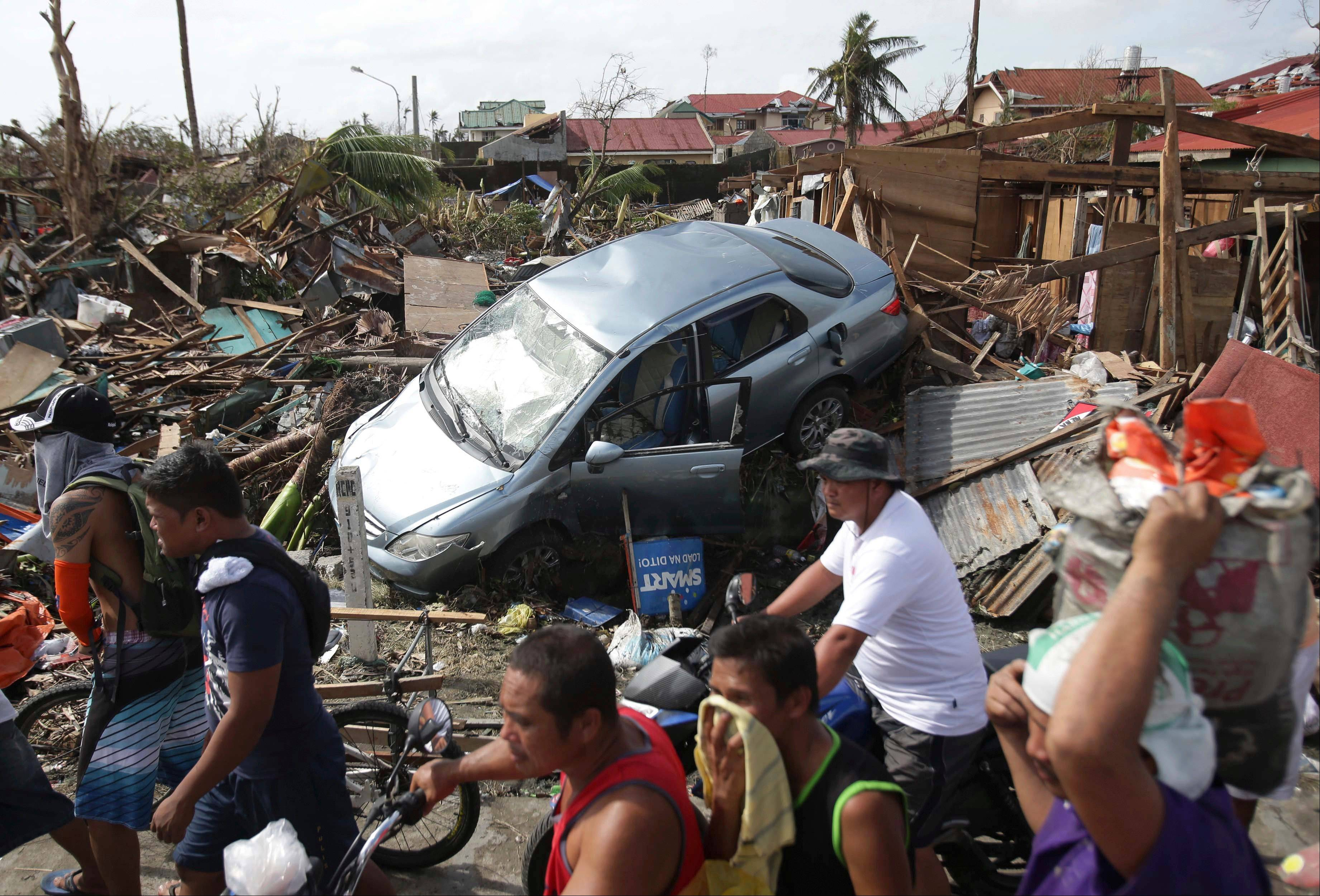 Survivors move past the damages caused by Typhoon Haiyan in Tacloban city, Leyte province central Philippines on Monday,.