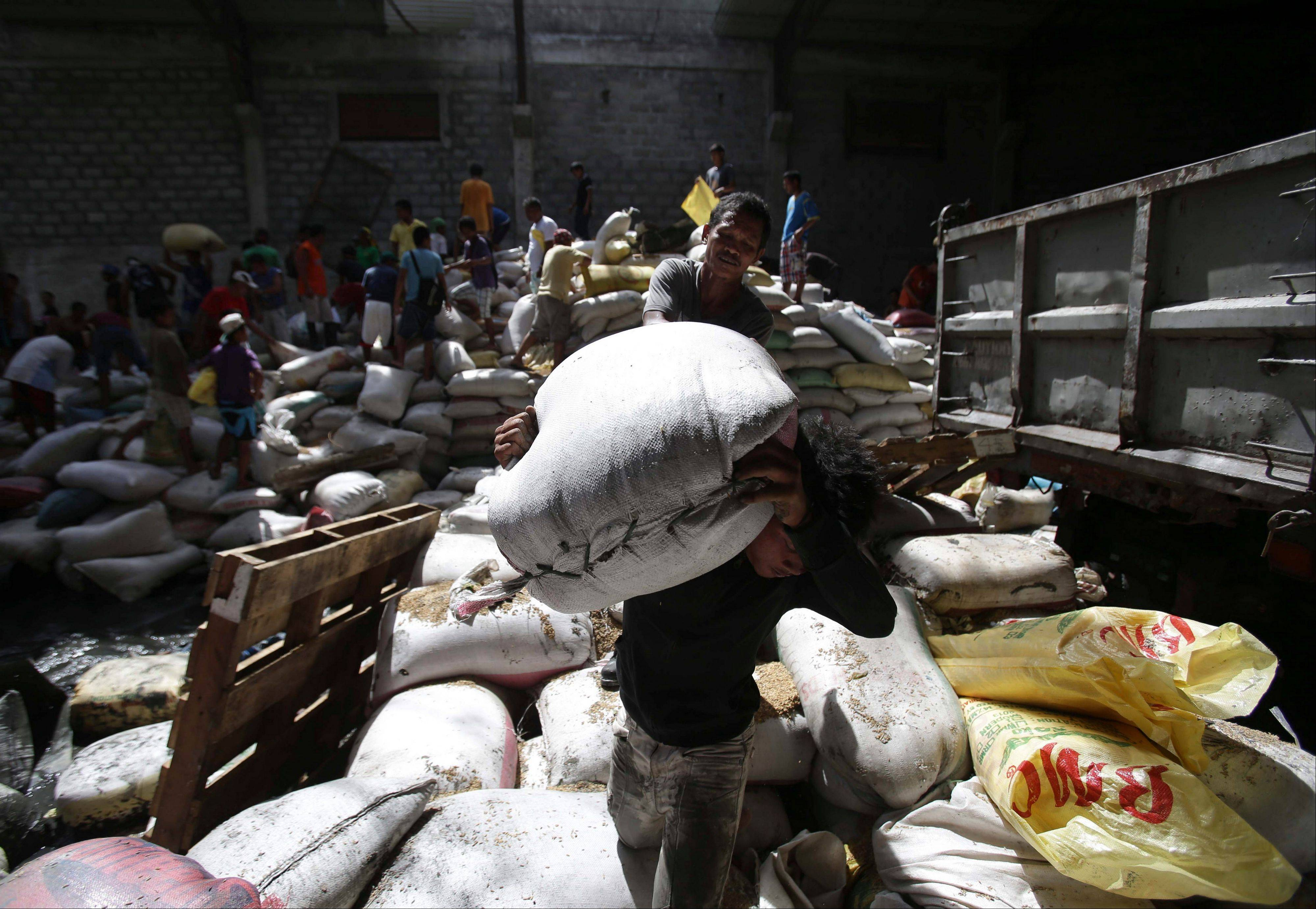 Survivors carry bags of rice from a warehouse which they stormed due to shortage of food at typhoon-ravaged Tacloban city, Leyte province central Philippines on Monday.
