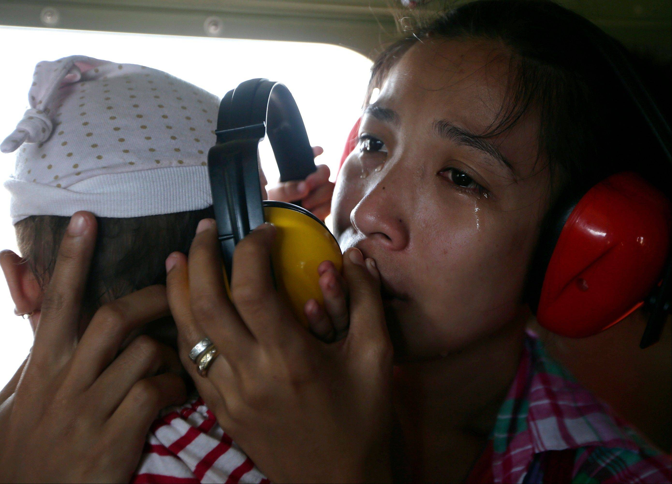 A mother cries in relief upon boarding a Philippine Air Force helicopter, Monday