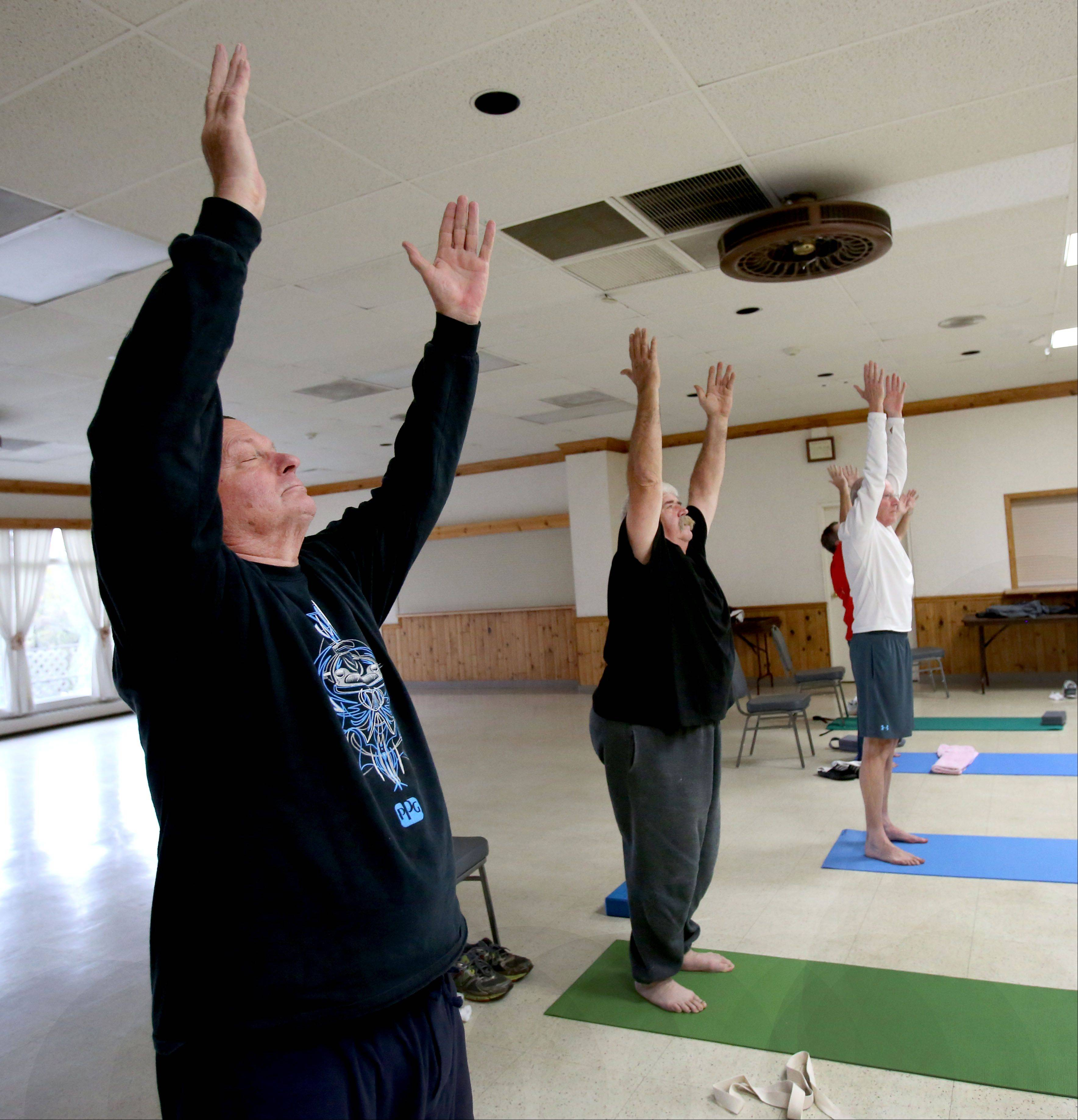 Mike Barbour of Naperville completes a sun salutation during a free yoga class for veterans at Judd Kendall VFW Post 3873 in Naperville. Barbour, a Vietnam veteran who said he suffers from post-traumatic stress disorder, said he helped volunteer instructor Dana Fish start the classes because he believes medications may not be the best way to treat the mental and physical problems veterans face after war.