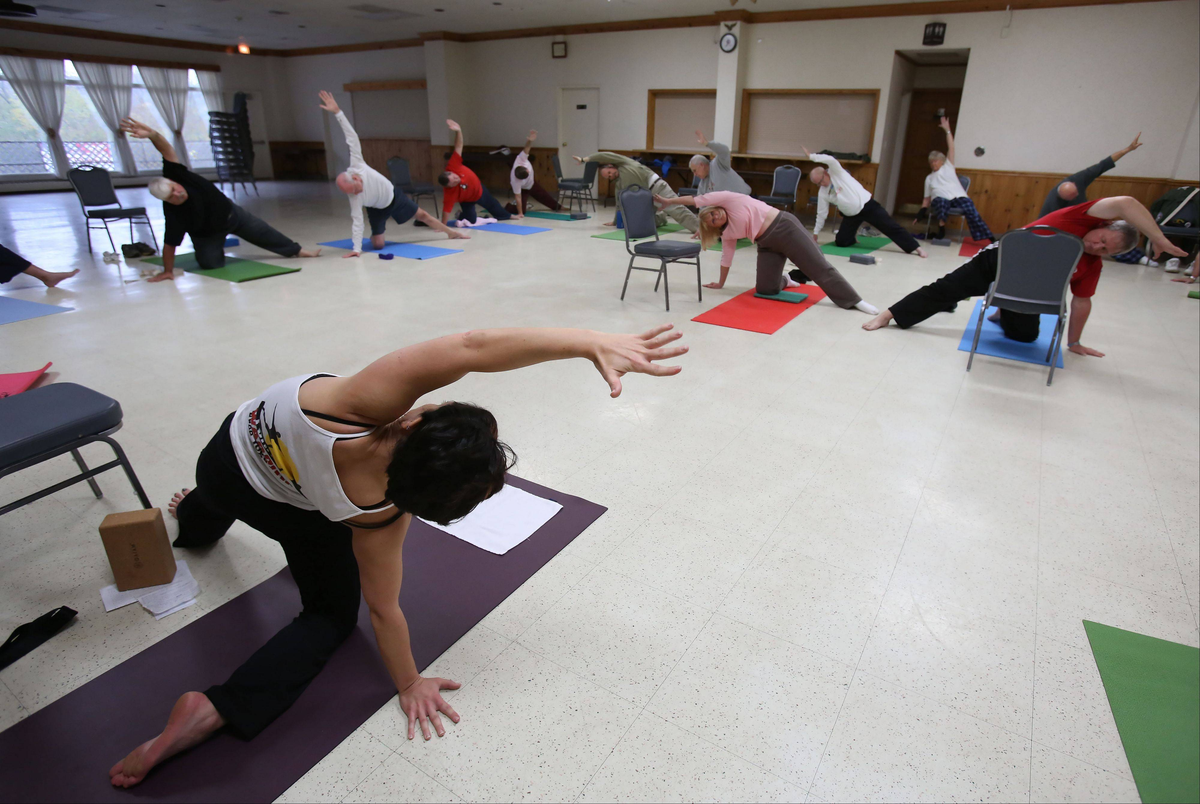 Dana Fish of Naperville guides about 20 Naperville-area veterans through a free yoga class at Judd Kendall VFW Post 3873 in Naperville. Fish has been trained by Connected Warriors to teach yoga in a manner that's accessible and supportive for military veterans.