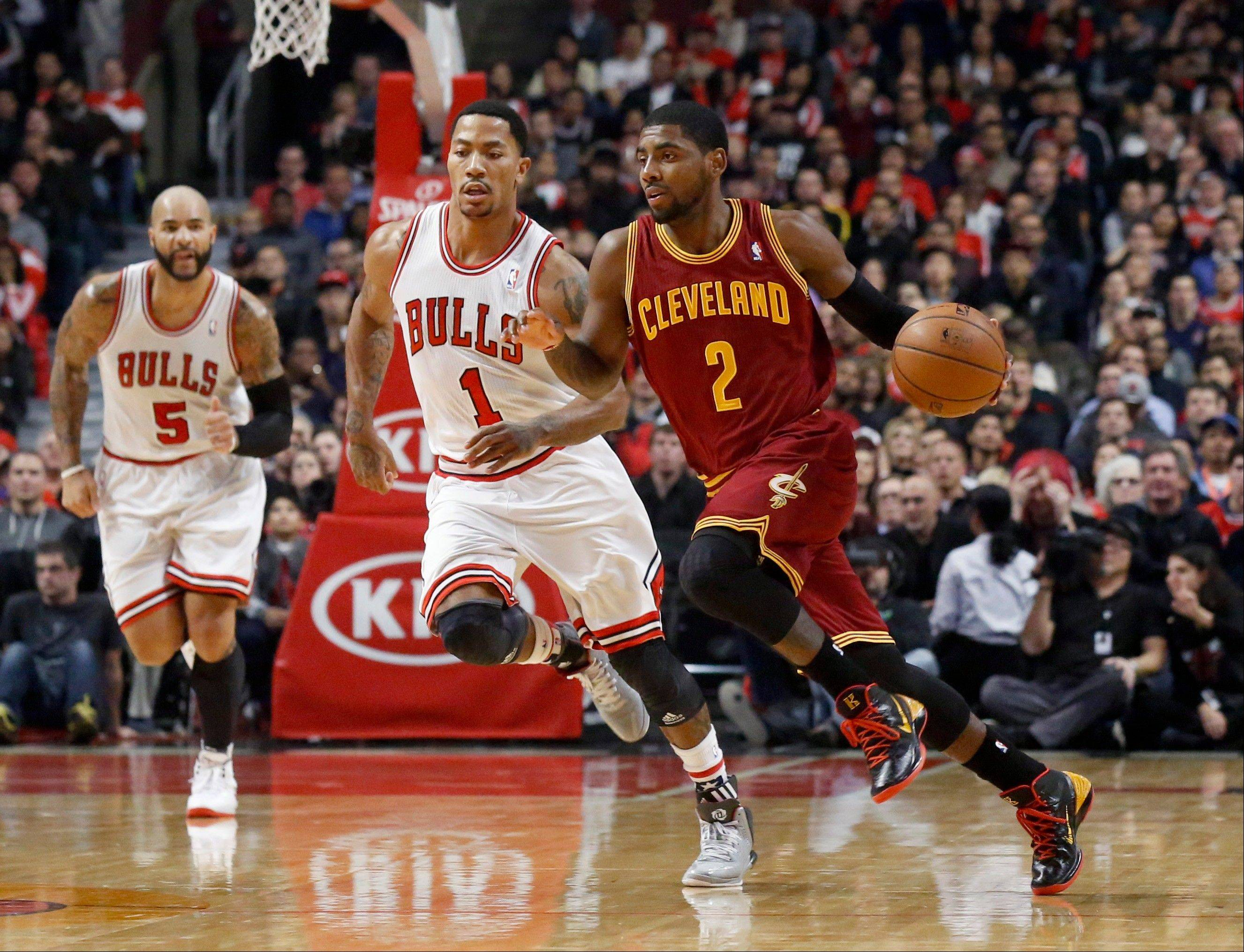 Cavaliers guard Kyrie Irving brings the ball up court as the Bulls' Derrick Rose defends Monday night.