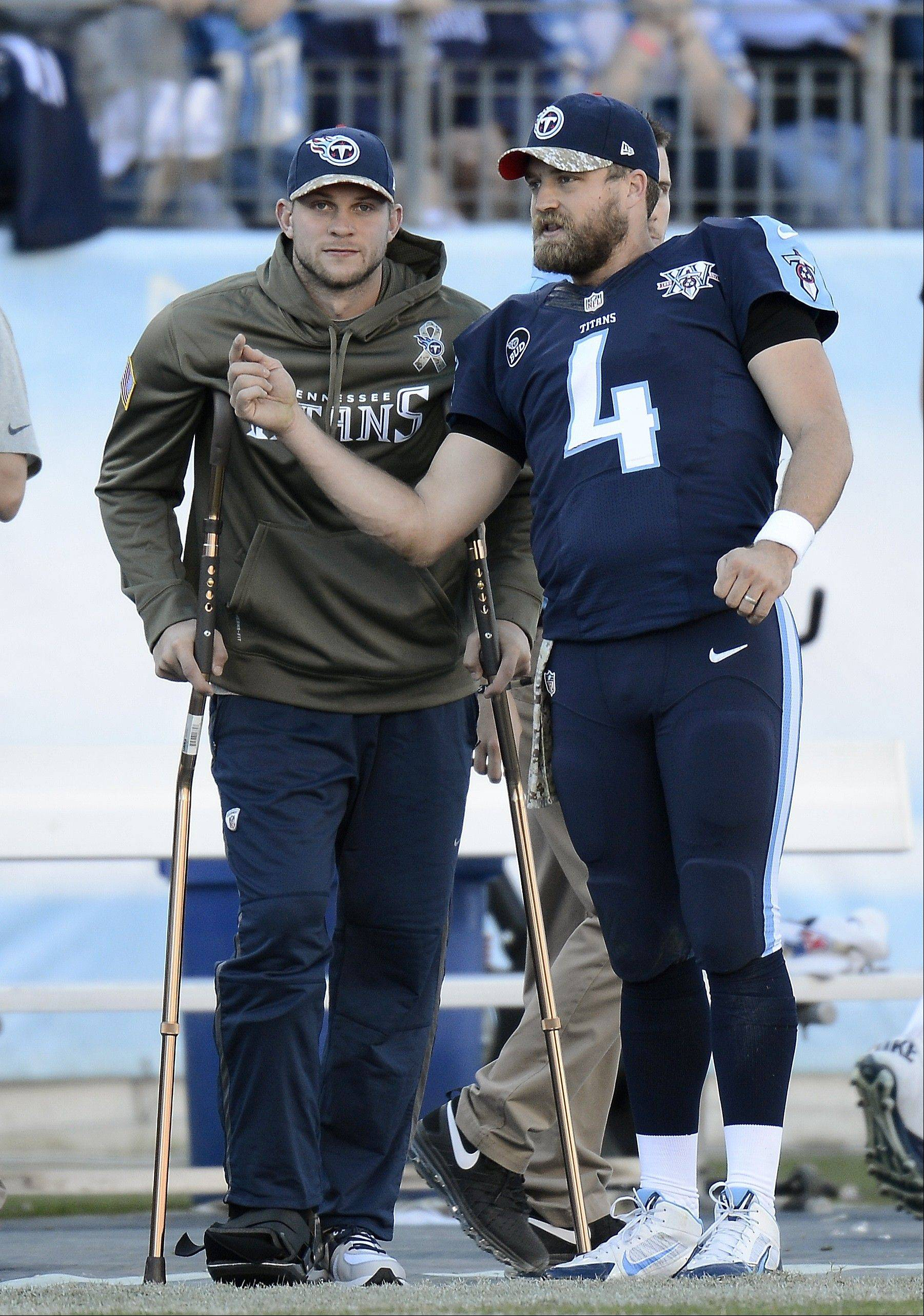 Tennessee Titans quarterback Jake Locker, left, watches from the sideline as he talks with fellow quarterback Ryan Fitzpatrick in the fourth quarter of Sunday's loss to Jacksonville.