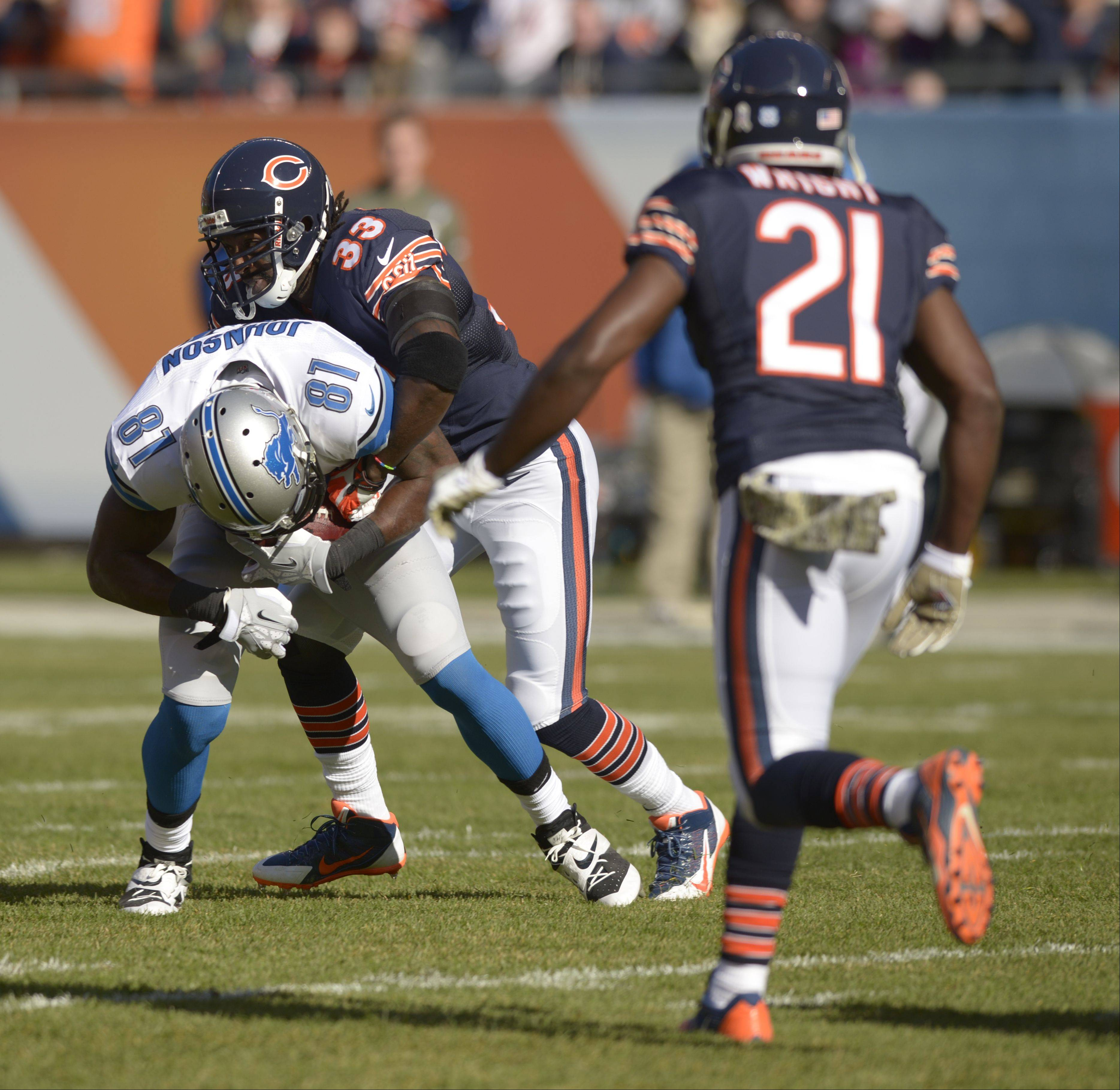 Detroit Lions wide receiver Calvin Johnson is taken down by Bears cornerback Charles Tillman during the Bears 21-19 loss to the Detroit Lions at Soldier Field, Sunday. Tillman injured a triceps in the game and will miss the rest of the regular season.