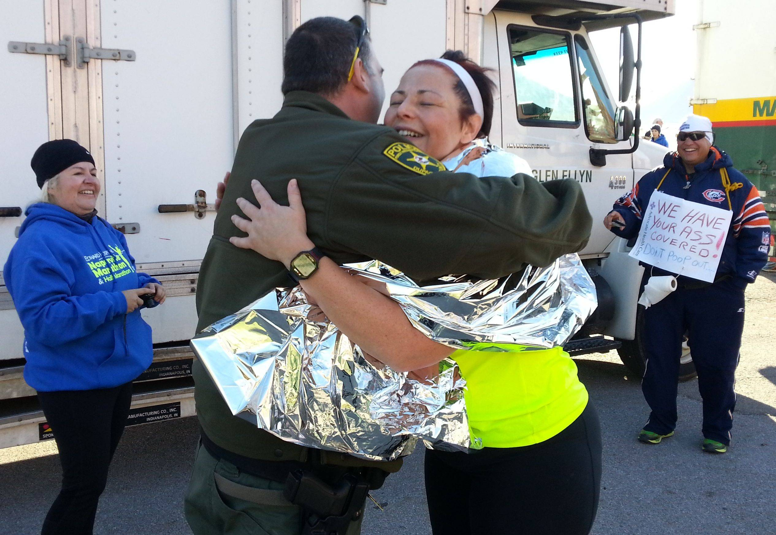 Naperville Marathon runner Kathy Contreras of Aurora embraces DuPage County Forest Preserve District police officer Lou Addante, who helped guide her to the finish line Sunday after she became lost during her seven-hour run.
