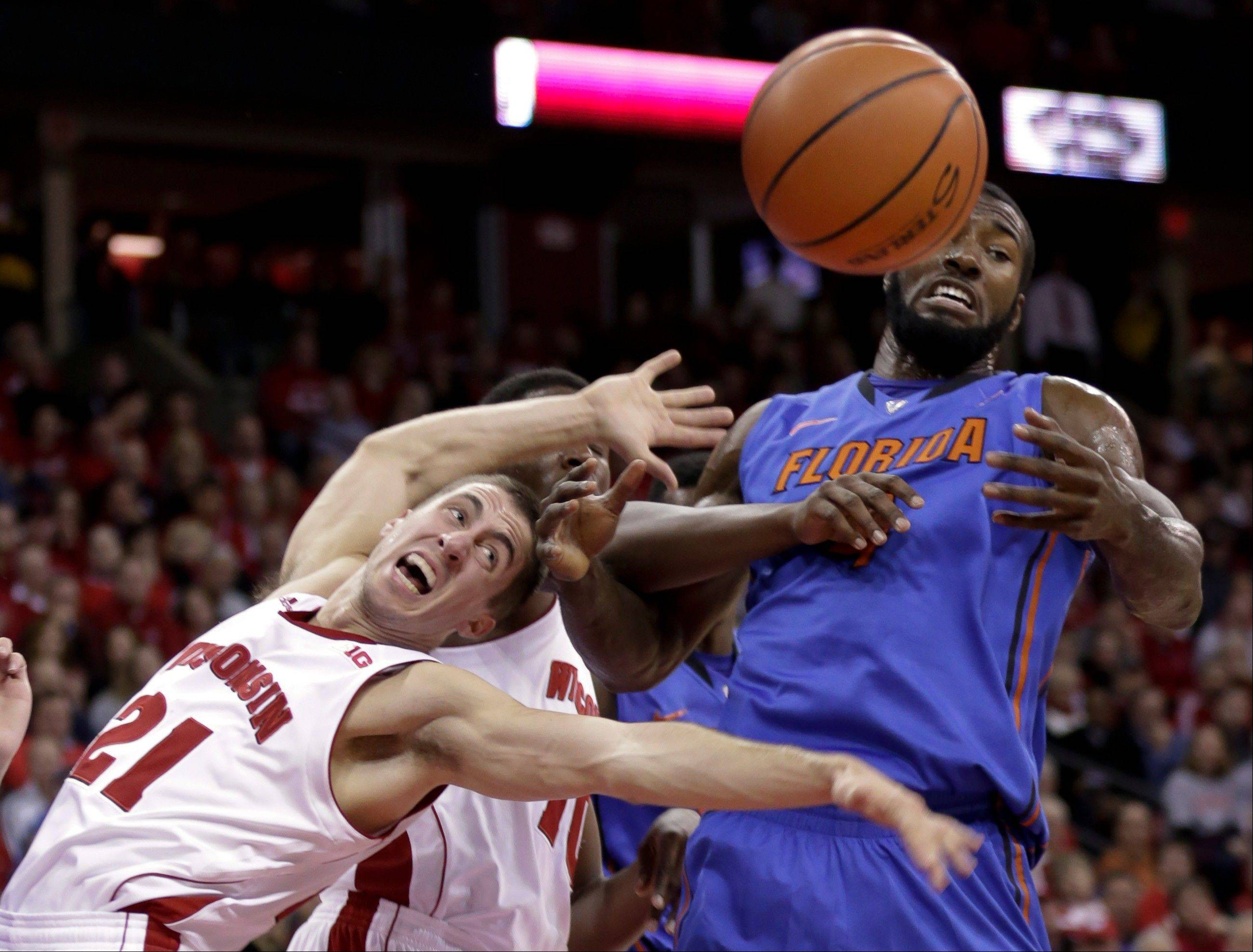 Wisconsin�s Josh Gasser (21) and Nigel Hayes vie for a rebound with Florida�s Patric Young during the first half of Tuesday�s game in Madison, Wis.
