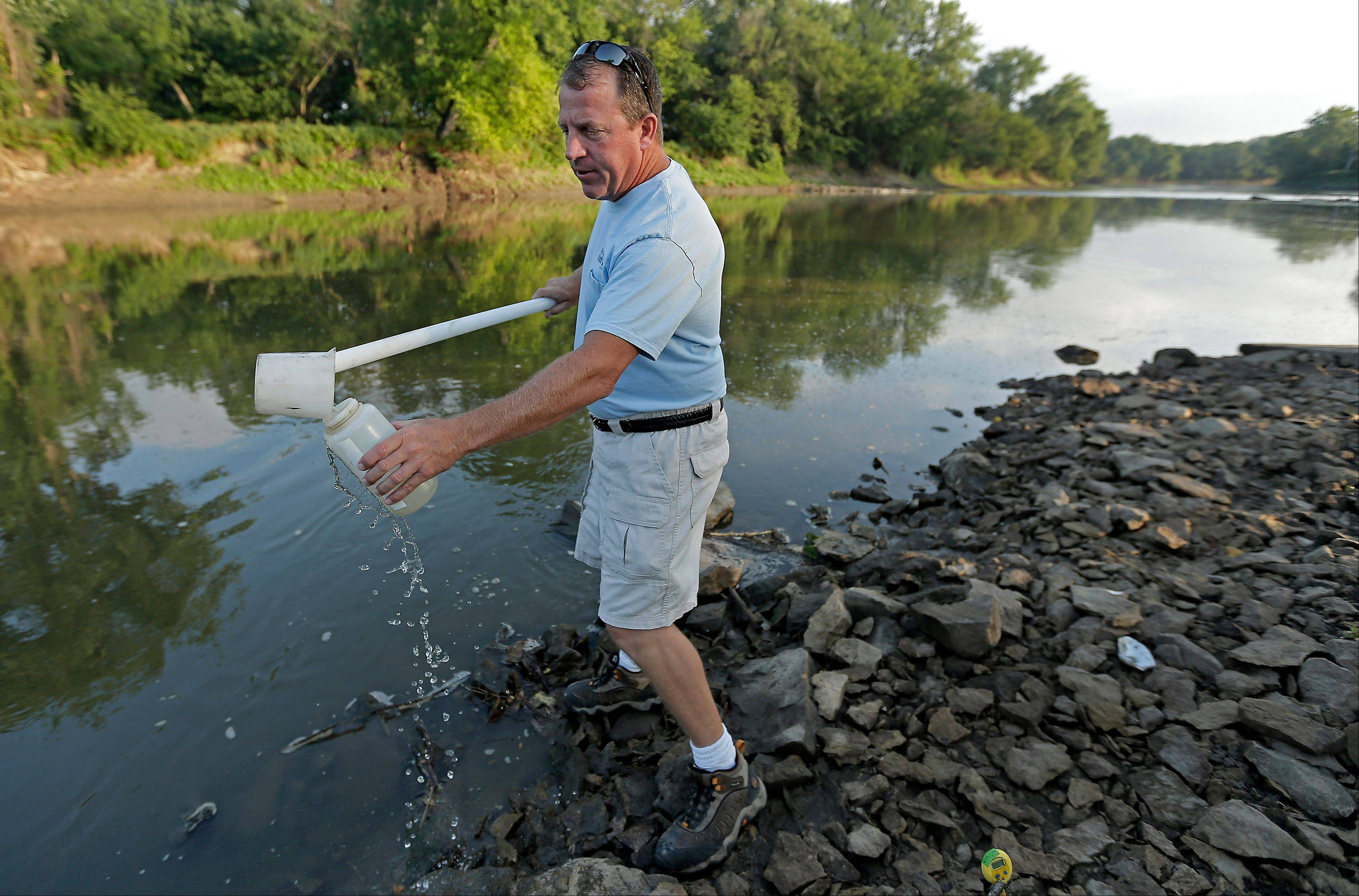 In this July 26, 2013, photo, Des Moines Water Works lab technician Bill Blubaugh takes a water sample from the Raccoon River in Des Moines. The water works has faced high nitrate levels for many years in the Des Moines and Raccoon Rivers, which supply drinking water to 500,000 people and the mandate to increase ethanol production, with millions of acres of new row crops being planted, is helping to increase nitrate pollution in municipal water supplies like Des Moines.