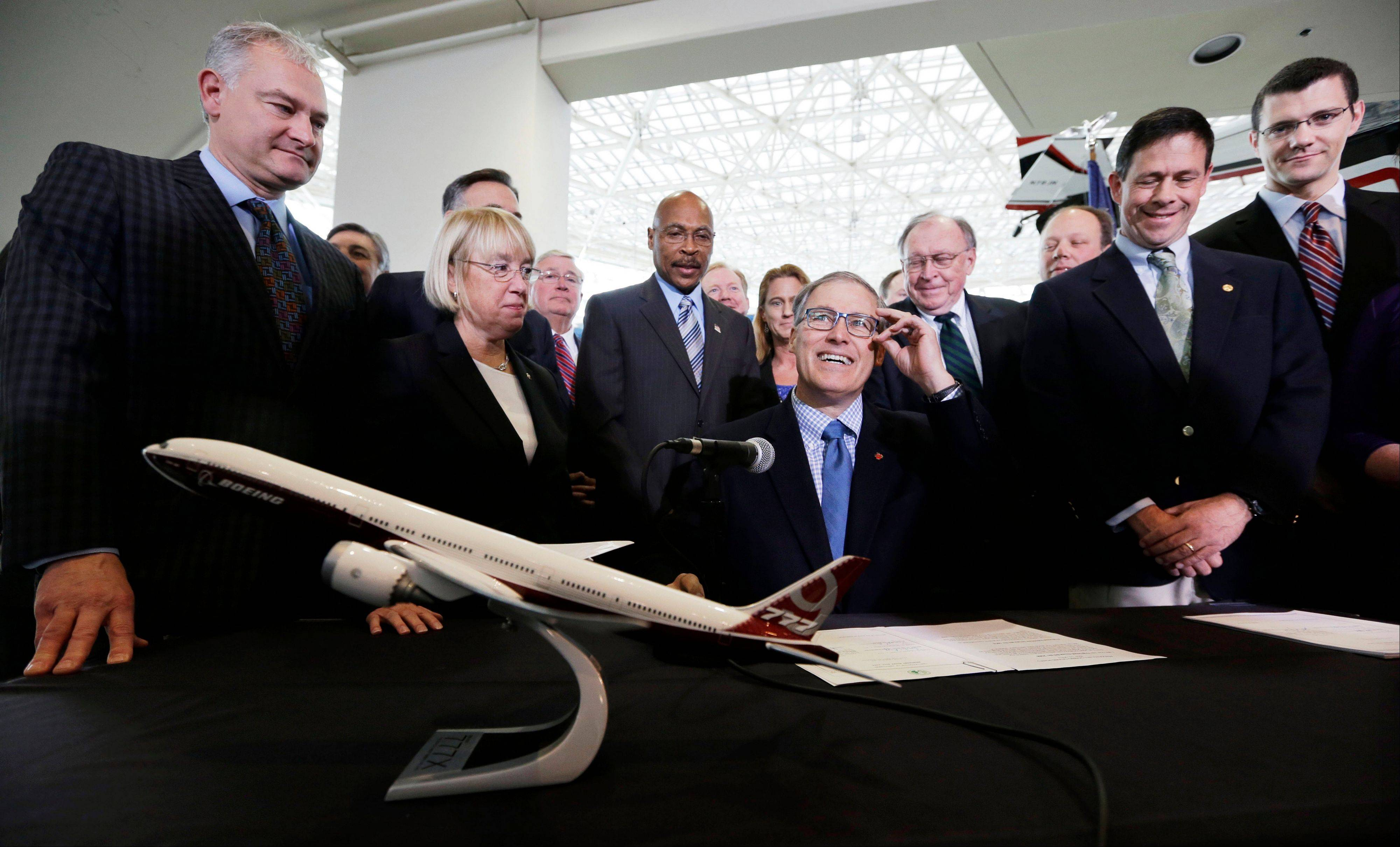 Gov. Jay Inslee, center, adjusts his glasses as he prepares to sign legislation to help keep production of Boeing's new 777X in Washington, Monday.