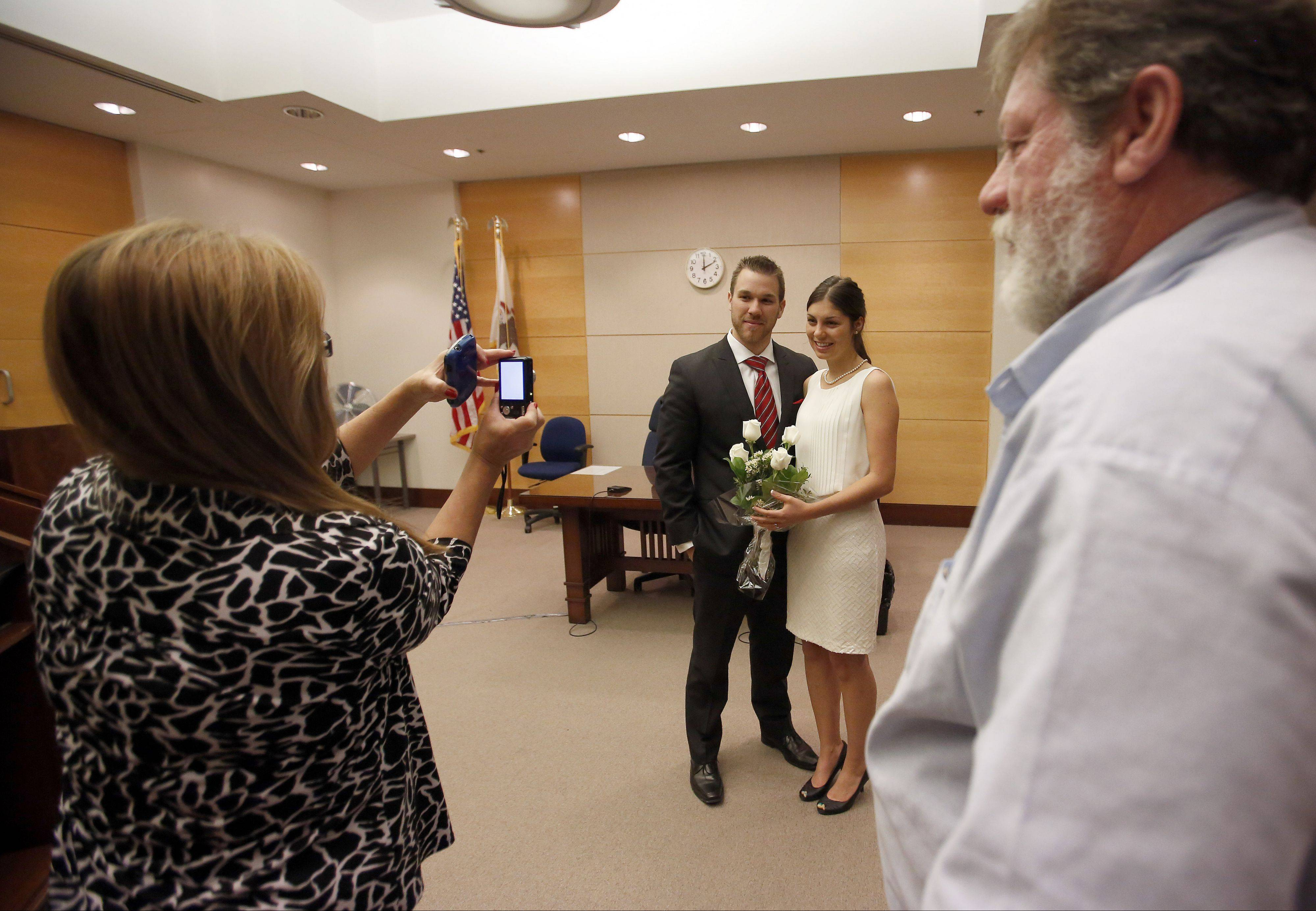 Robert Forrest of Kansas City, Kan., poses with his bride Katie Krueger of East Dundee after getting married at the Kane County Courthouse Tuesday, 11-12-13, in St. Charles. The couple, who met at church, have a busy week planned complete with a big move. Connie and Don Krueger, Katie's parents, take pictures after the ceremony.