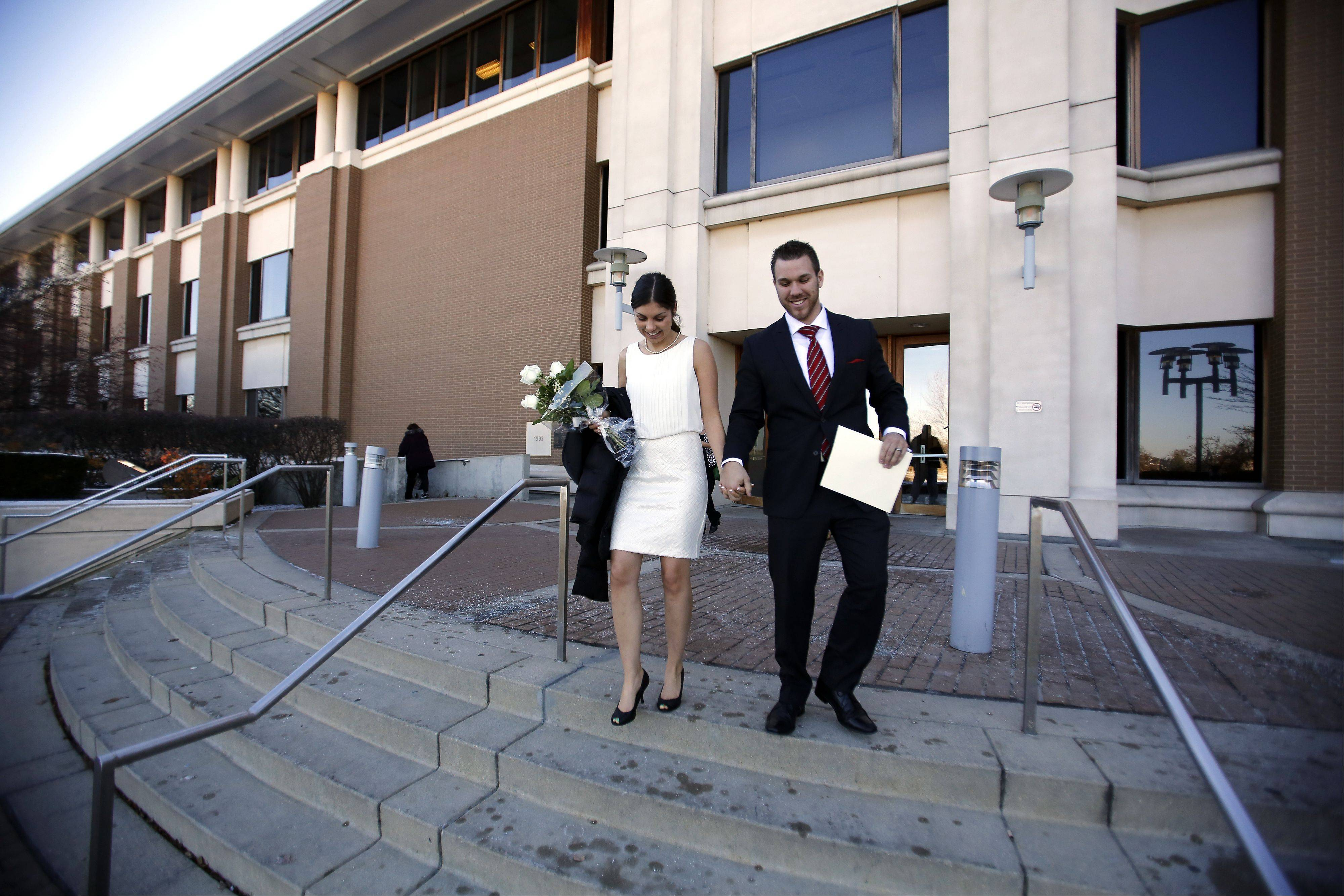 Robert Forrest of Kansas City, Kansas, and his bride Katie Krueger of East Dundee leave the courthouse with their marriage certificate in hand after getting married at the Kane County Courthouse on Tuesday, 11-12-13, in St. Charles.