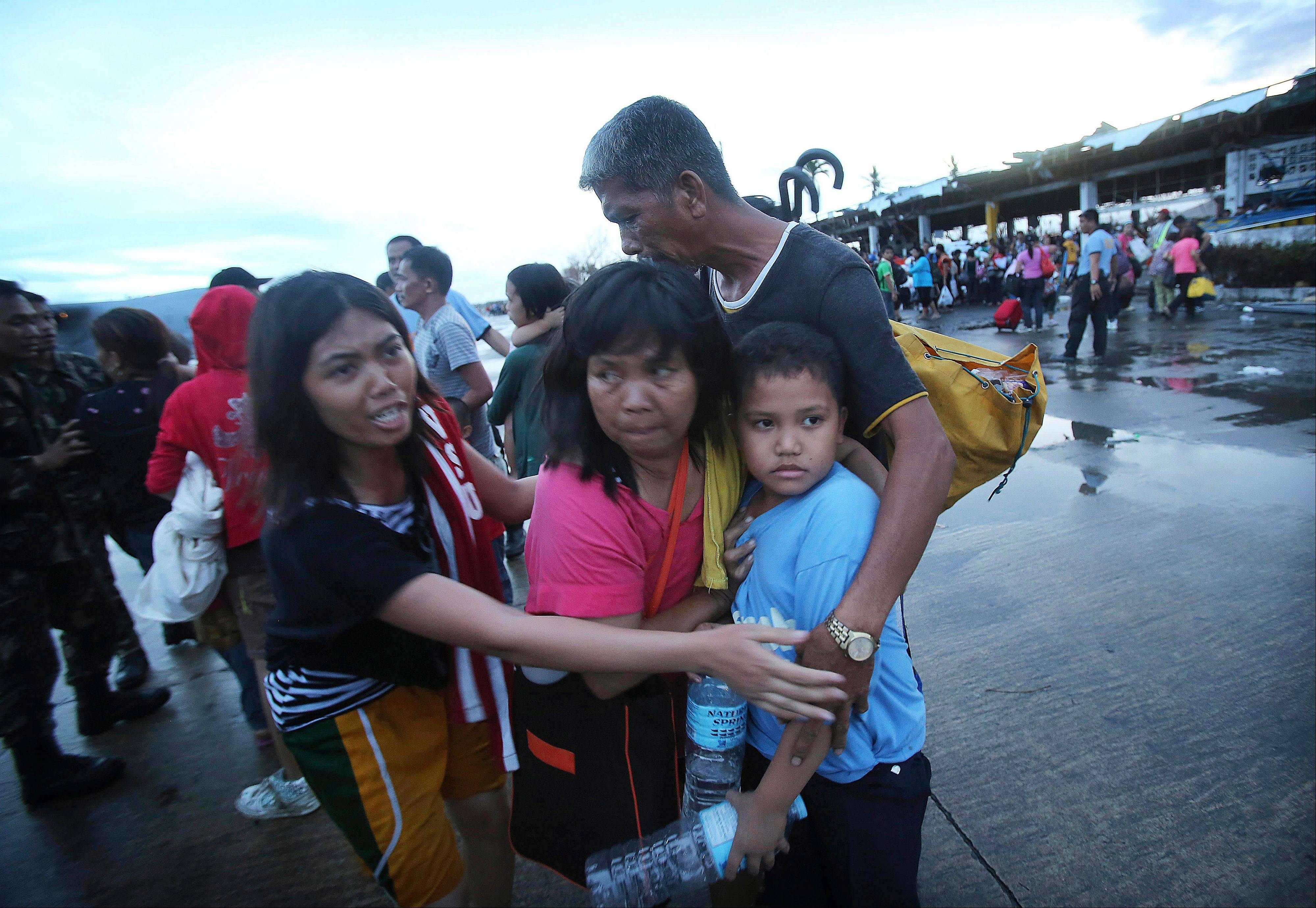 Survivors of Typhoon Haiyan comfort each other after not being allowed to board a C-130 cargo plane because of limited space Tuesday at the airport in Tacloban, central Philippines.