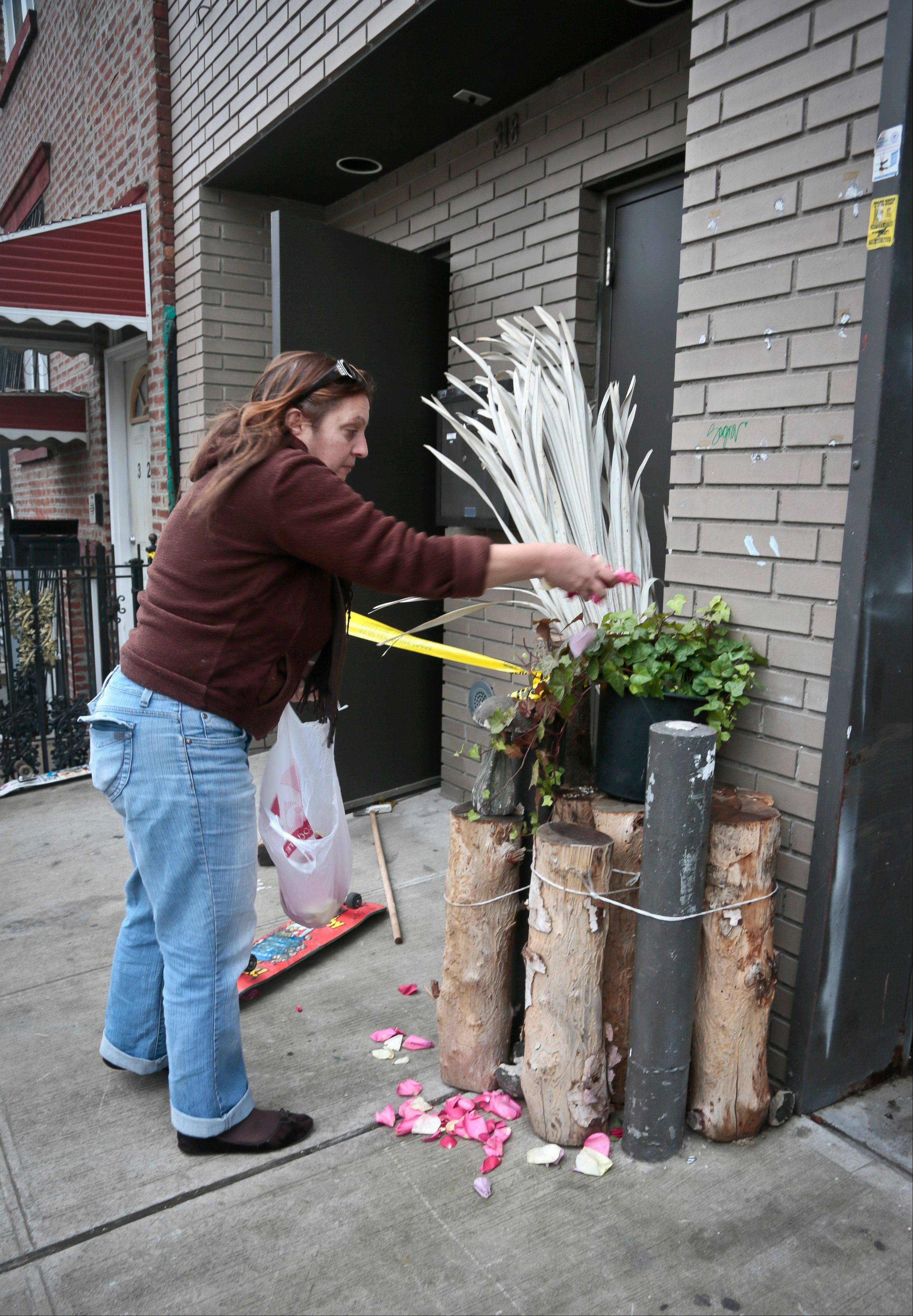 Joanne Bascetta scatters flower petals outside the apartment that was scene of a Monday shooting rampage, Tuesday, Nov. 12, 2013 in Brooklyn, New York. Police said gunman Ali Akbar Mahammadi Rafie, 29, a musician, killed himself on the roof after shooting to death two members of the Iranian indie rock band Yellow Dogs, a third musician and wounding a fourth person early Monday morning.
