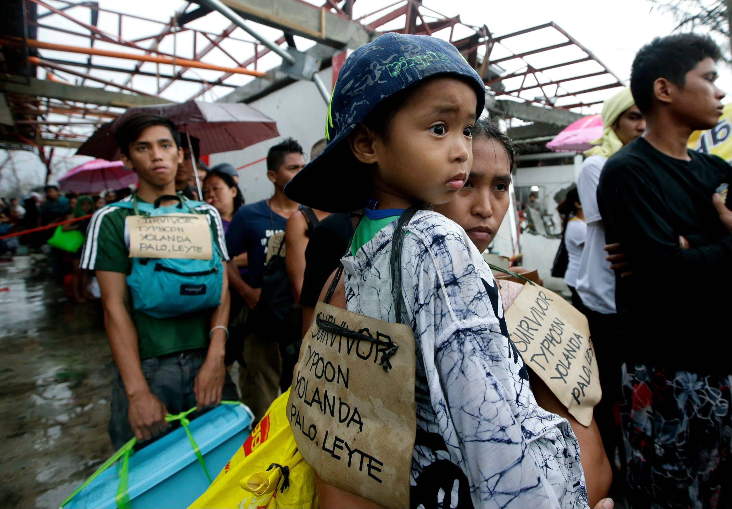 Typhoon survivors hang signs from their necks as they queue up in the hopes of boarding a C-130 military transport plane Tuesday in Tacloban, central Philippines. Thousands of typhoon survivors swarmed the airport on Tuesday seeking a flight out, but only a few hundred made it, leaving behind a shattered, rain-lashed city short of food and water and littered with countless bodies.