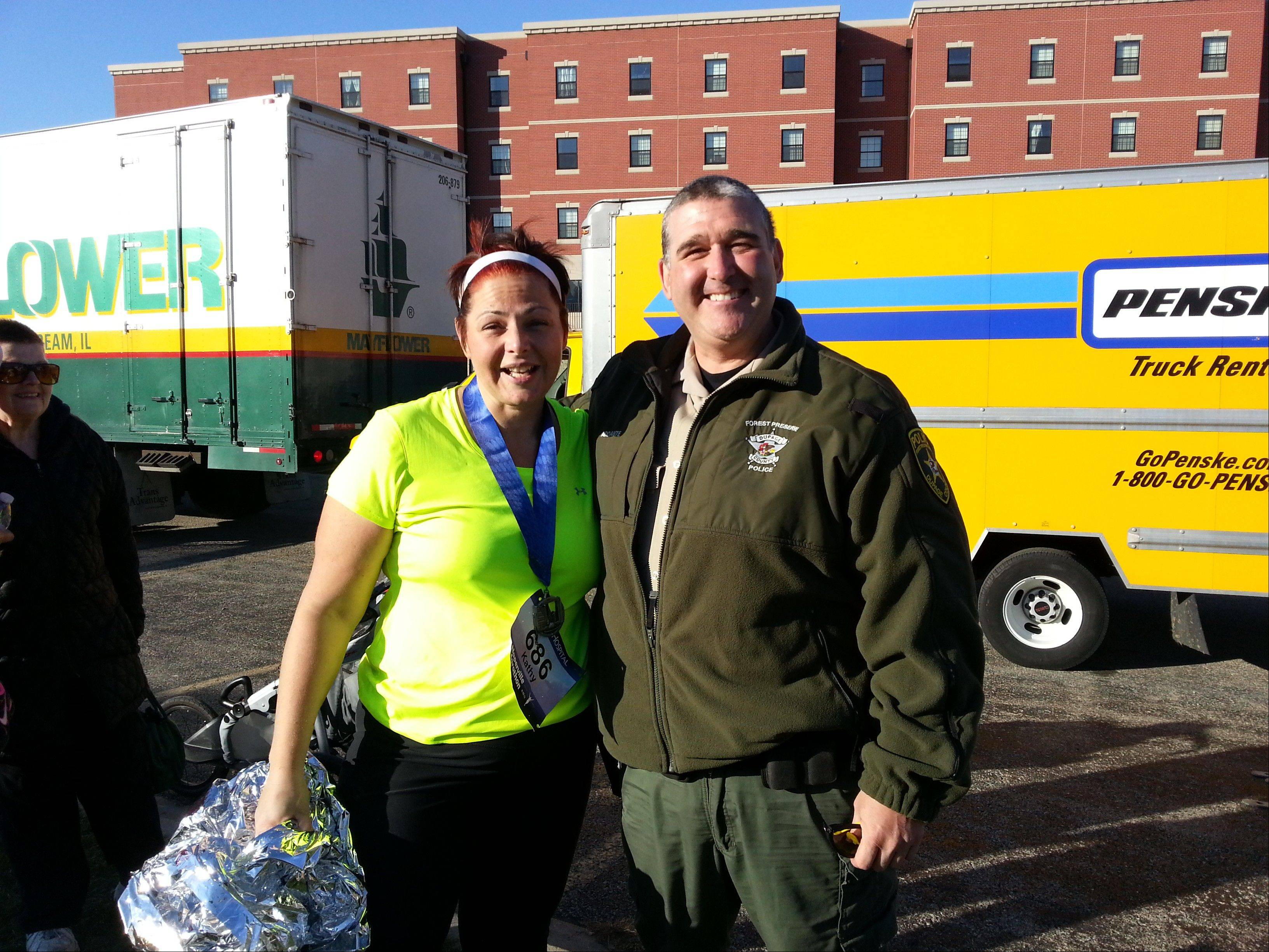 Naperville Marathon runner Kathy Contreras of Aurora smiles for a photo with DuPage County Forest Preserve District police officer Lou Addante after crossing the finish line. Addante was among a group of people who guided Contreras to the finish line Sunday after she became lost.
