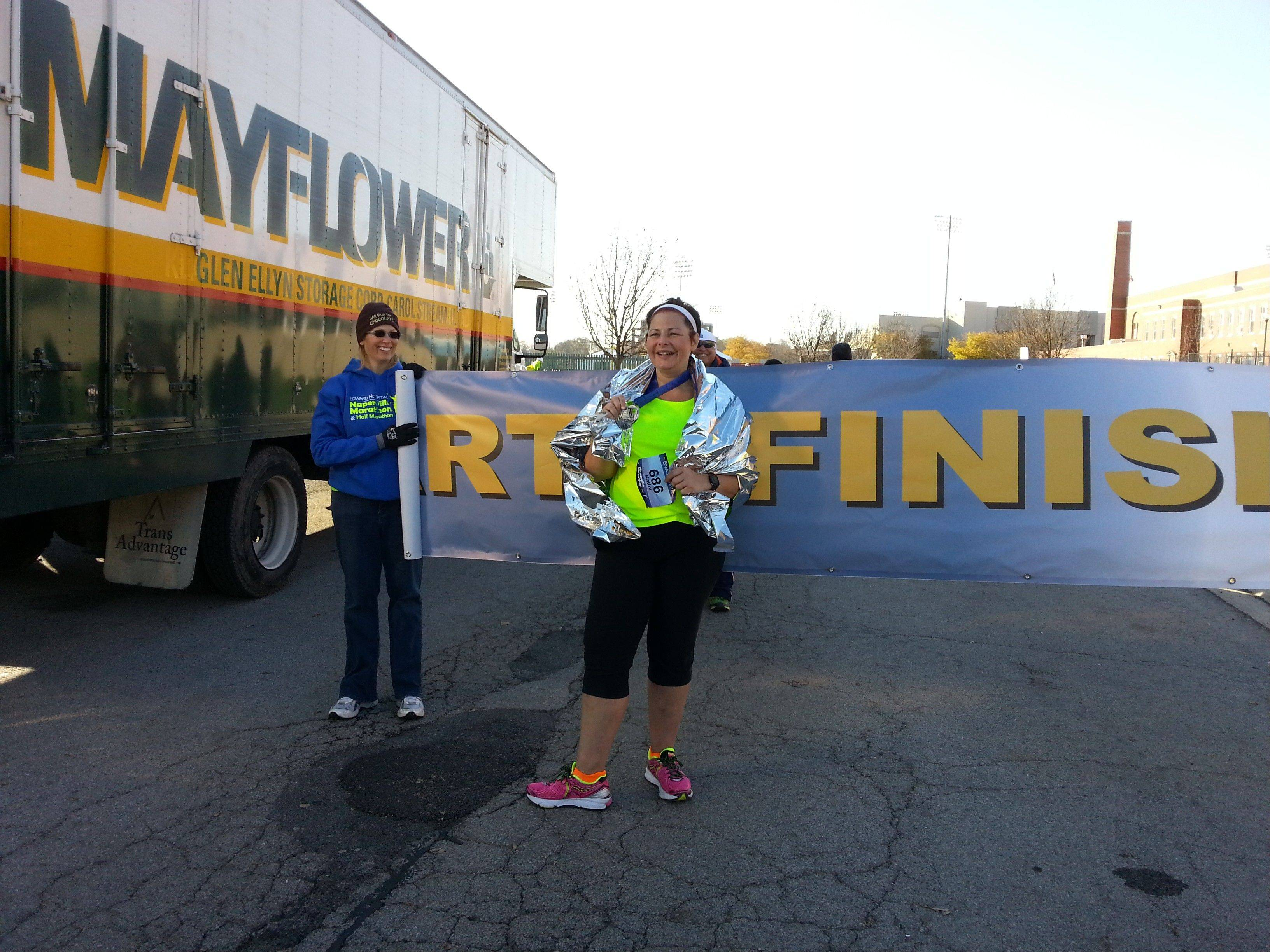 Naperville Marathon runner Kathy Contreras of Aurora celebrates her seven-hour finish Sunday.