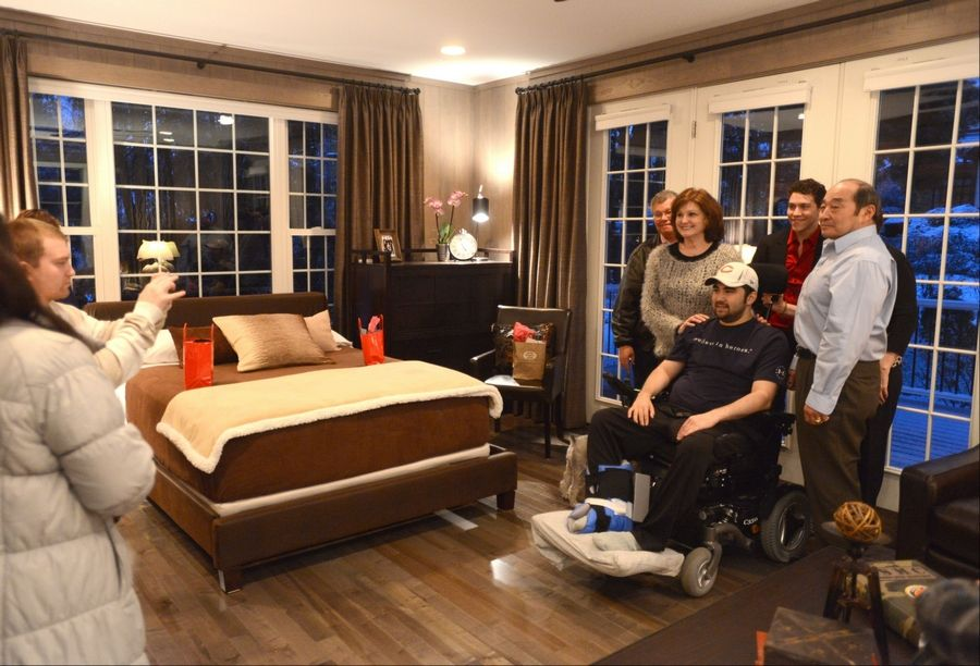 Iraq War veteran Dan Tsutsumi poses for pictures Monday with his mother and father as well as those who participated in the remodeling project at his parents' Arlington Heights home.