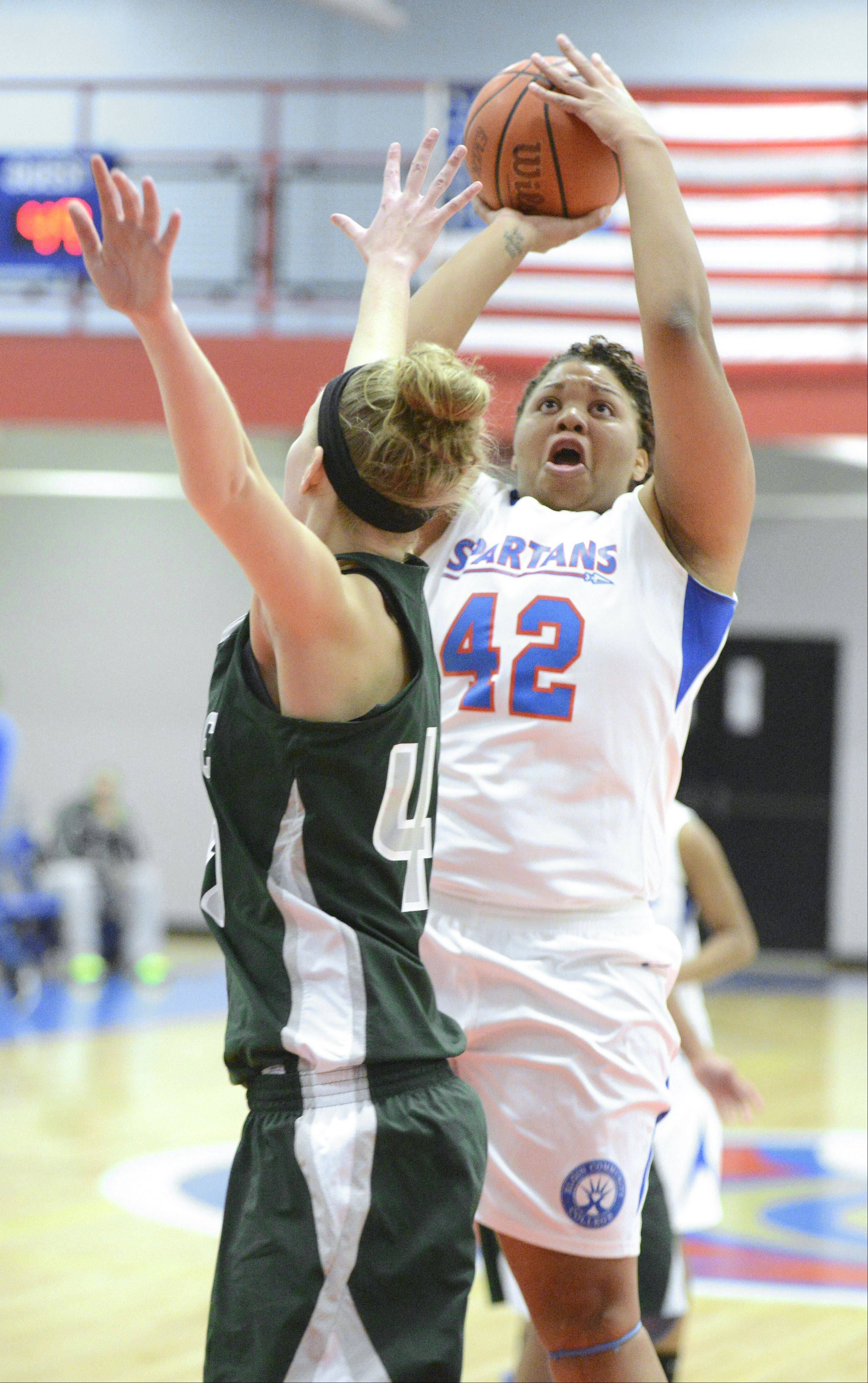 Elgin Community College's Porsche Griggs shoots over a block by College of DuPage's Melissa Niggins in the second half on Tuesday in Elgin.