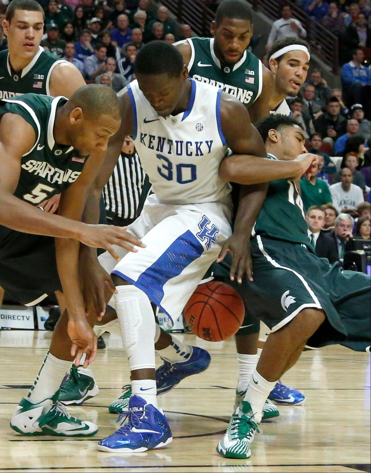 Michigan State center Adreian Payne (5), Kentucky forward Julius Randle (30) and Michigan State guard Gary Harris, right, struggle for a loose ball during the first half of an NCAA college basketball game Tuesday, Nov. 12, 2013, in Chicago.