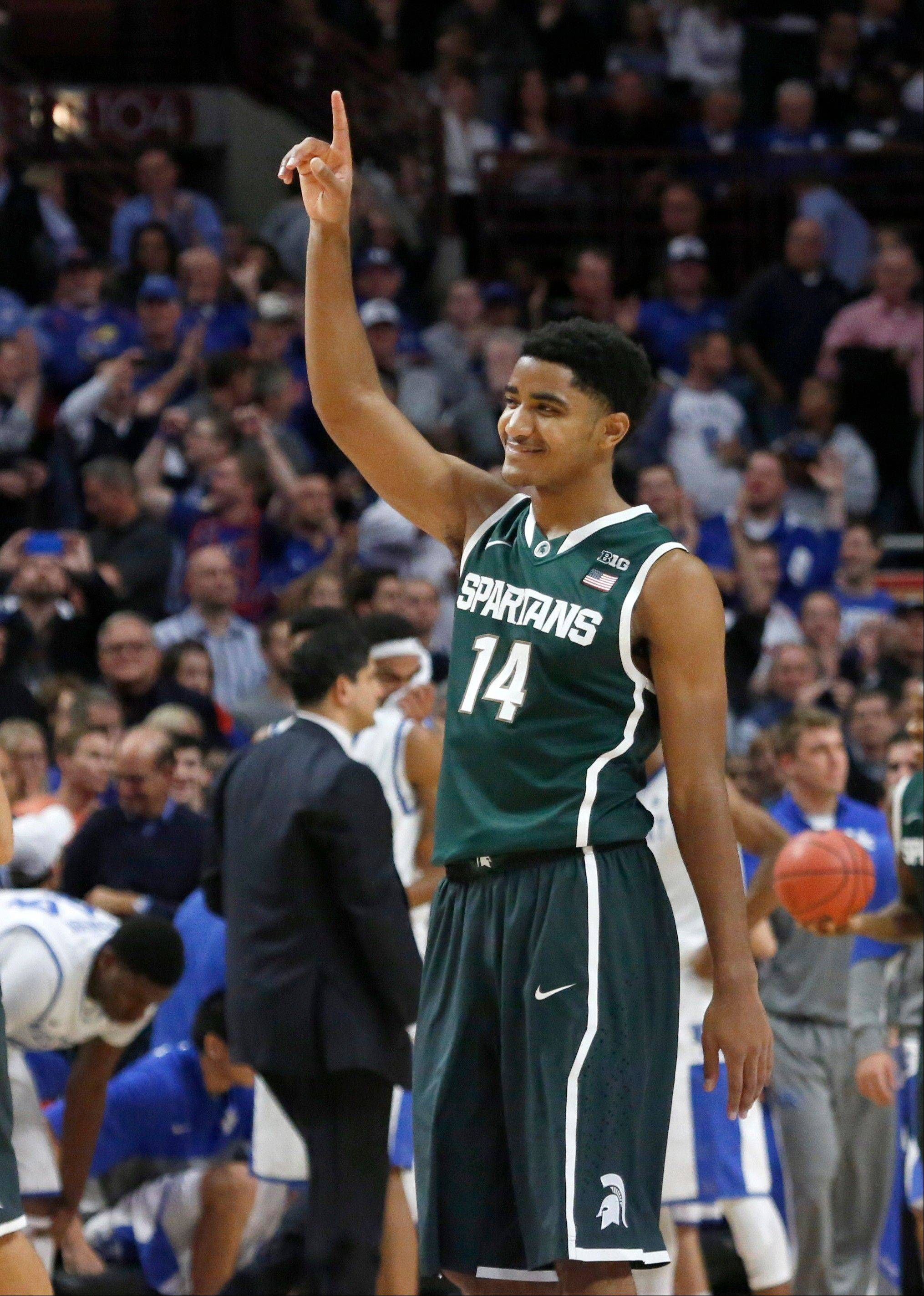 Michigan State guard Gary Harris (14) celebrates the Spartans' 78-74 win over Kentucky in an NCAA college basketball game Tuesday, Nov. 12, 2013, in Chicago.