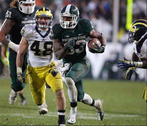Michigan State's Jeremy Langford runs between Michigan's Desmond Morgan (48) and Raymon Taylor for a 40-yard touchdown during the Nov. 2 game in East Lansing. The No. 14 Spartans can clinch at least a share of the Legends Division title with a victory at Nebraska on Saturday,