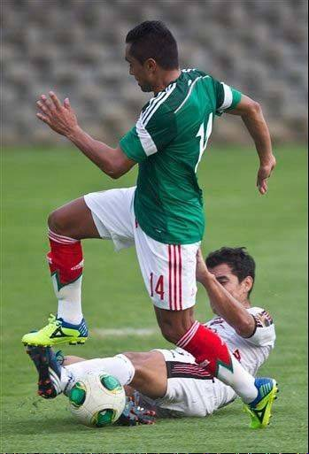 Mexico's Edwin Hernandez, top, fights for the ball with Lobos' Manuel Mondragon during a friendly soccer match Saturday. Mexico will play New Zealand twice for a spot in next year's World Cup. Mexico will host the first leg on Nov. 13 and play at New Zealand on Nov. 20.